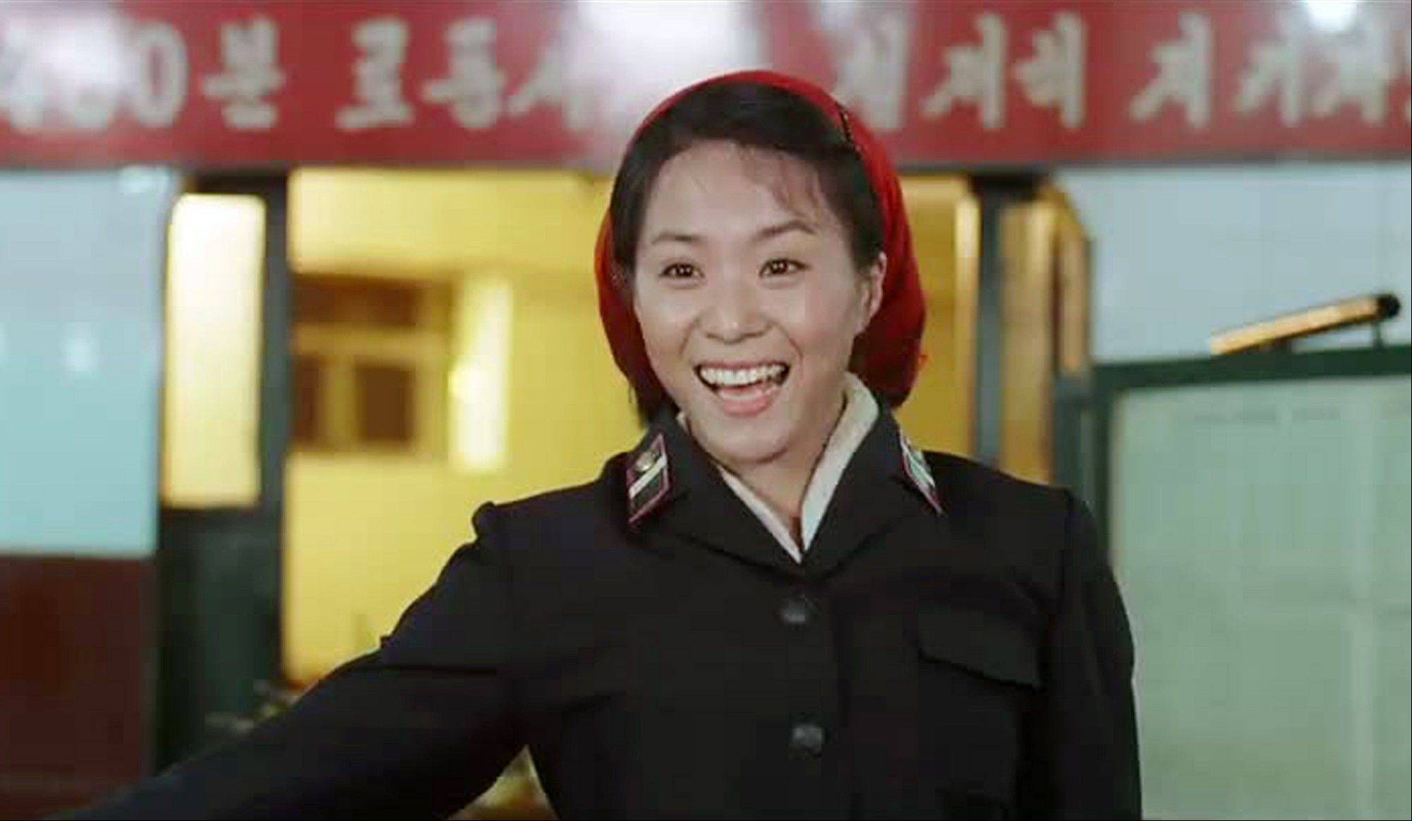 In this image made out of film �Comrade Kim Goes Flying,� released by Another Dimension of An Idea/Koryo Group, Comrade Kim Yong Mi played by Han Jong Sim acknowledges applause from her comrades for her acrobatic performance.