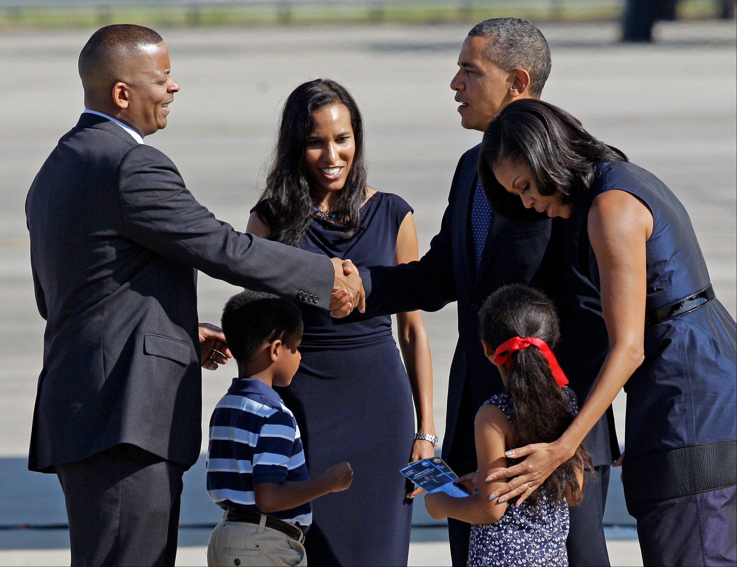 President Barack Obama shakes hands with Charlotte, N.C. Mayor Anthony Foxx, left, as first lady Michelle Obama, right, greets Foxx�s children Hillary, and Zachary, before leaving leave Charlotte, N.C., after the Democratic National Convention, Friday, Sept. 7, 2012. Foxx�s wife Samara Foxx is second from left.