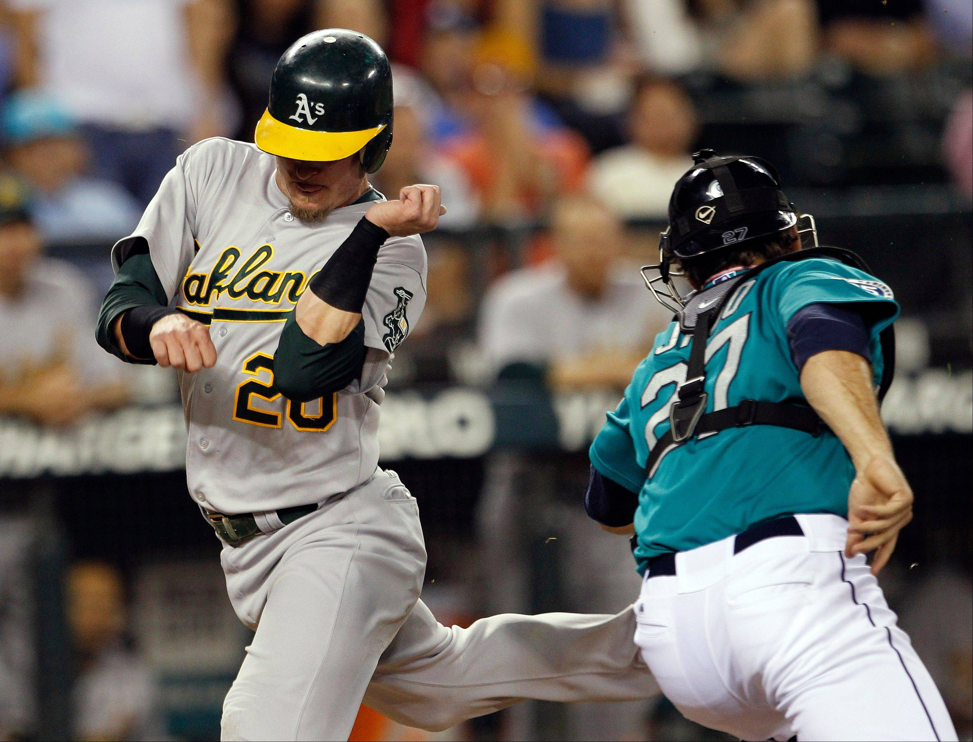 Oakland�s Josh Donaldson crosses home just ahead of a tag by Mariners catcher John Jaso in the fifth inning Friday in Seattle.
