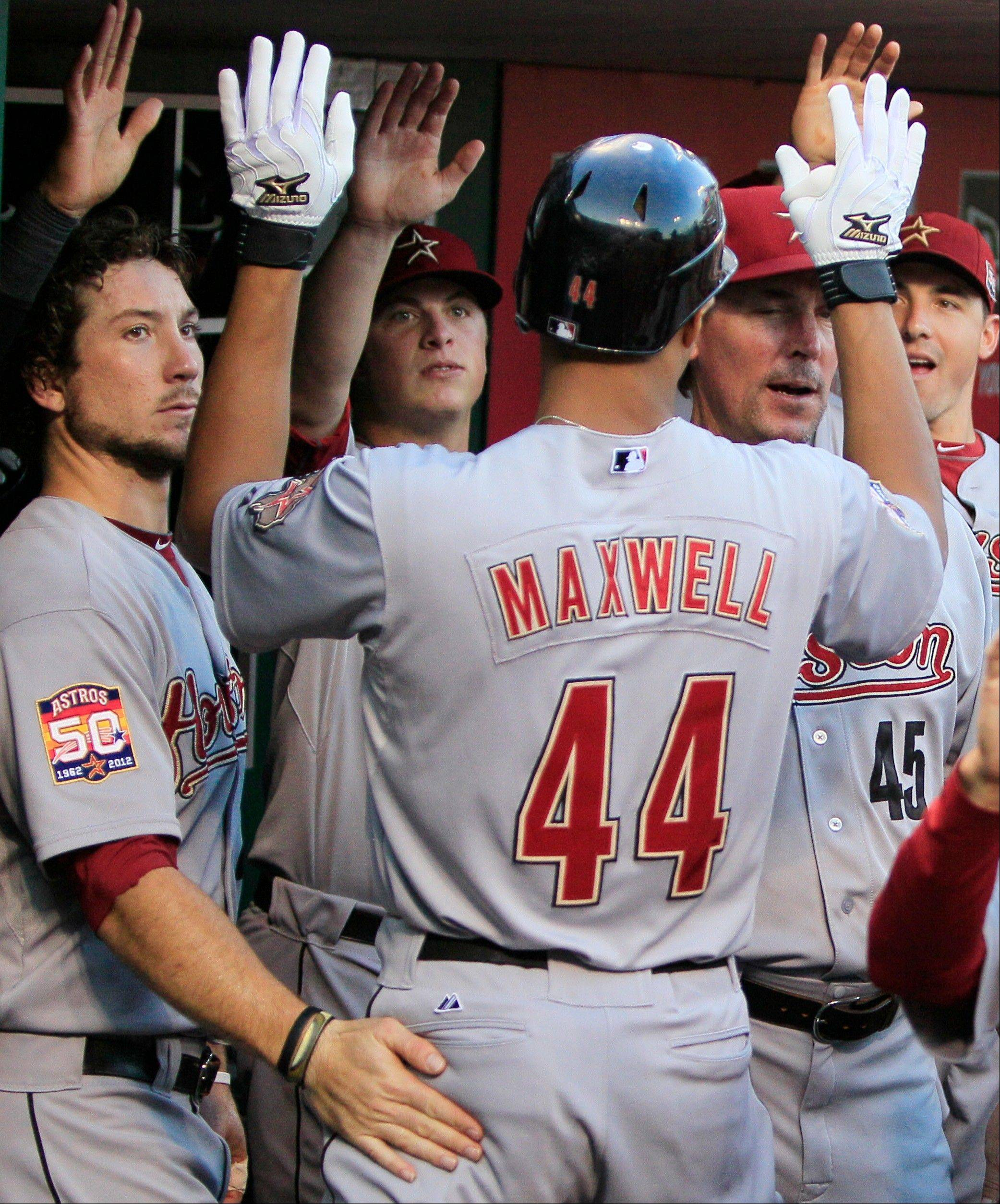 Houston�s Justin Maxwell celebrates in the dugout after hitting a two-run home run in the first inning Friday in Cincinnati.
