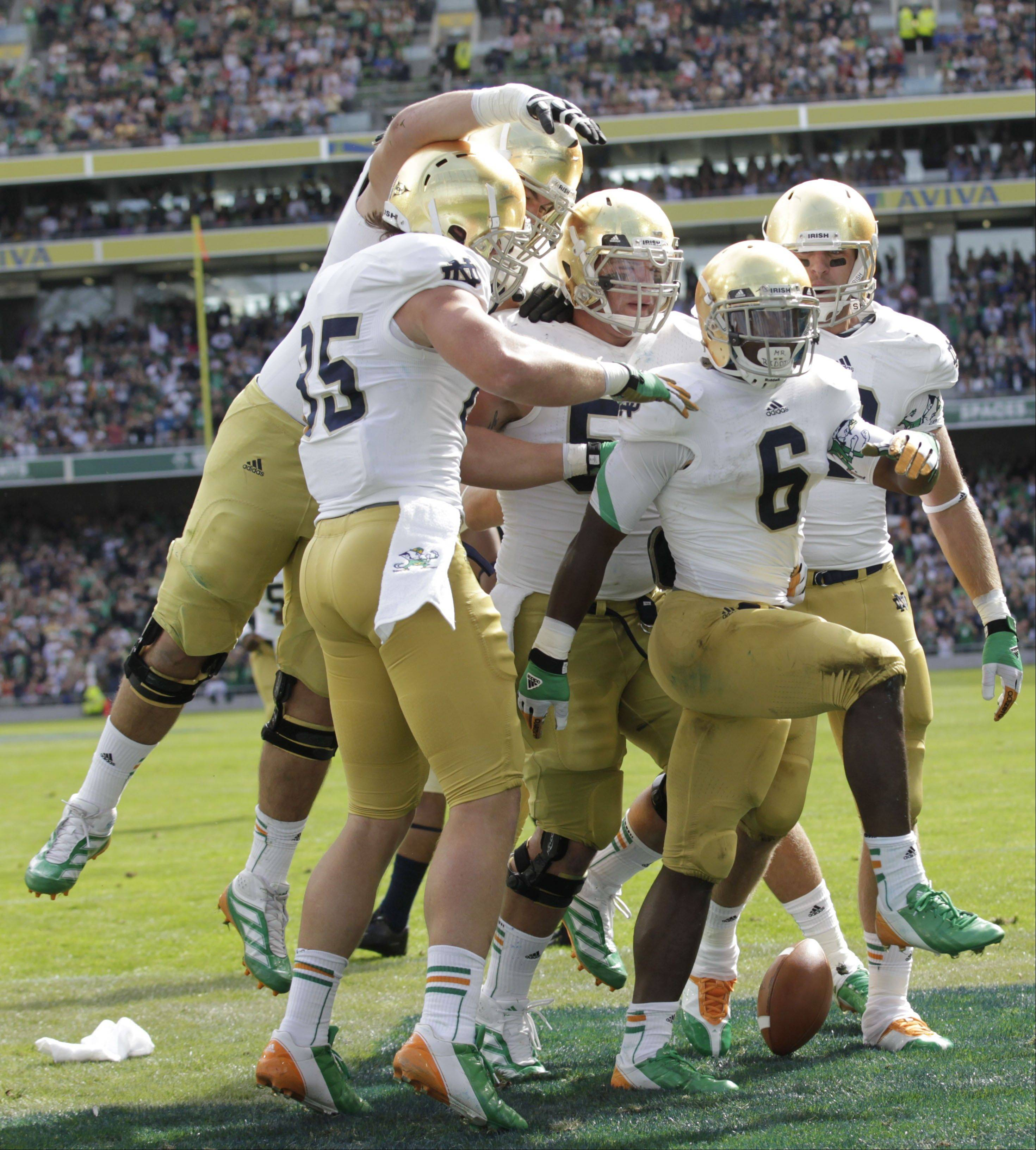 Notre Dame�s Theo Riddick, right, celebrates with teammates after scoring a touchdown against Navy last Saturday in Dublin, Ireland.