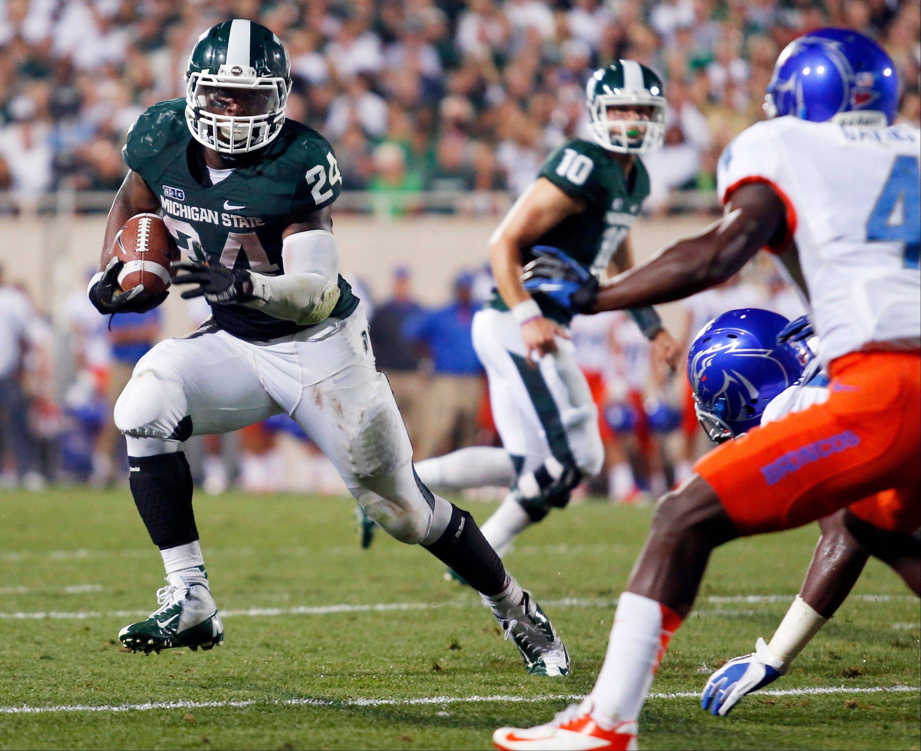 Michigan State�s Le�Veon Bell gets past Boise State�s Jerell Gavins to score the game-winning touchdown last Saturday in East Lansing, Mich.