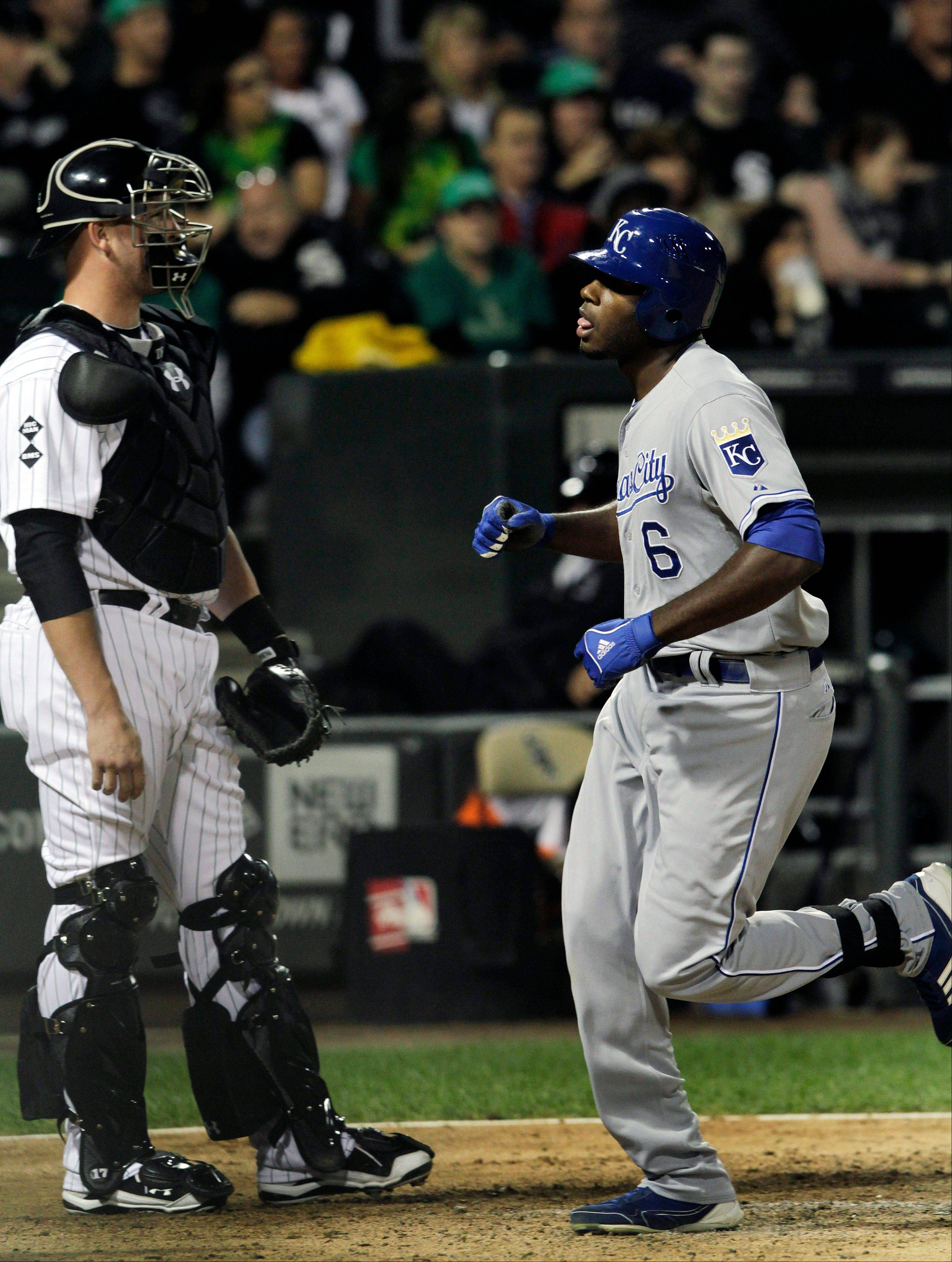 Royals� Lorenzo Cain cross home plate in front of White Sox catcher Tyler Flowers after hitting a 2-run homer in the ninth inning Friday night.