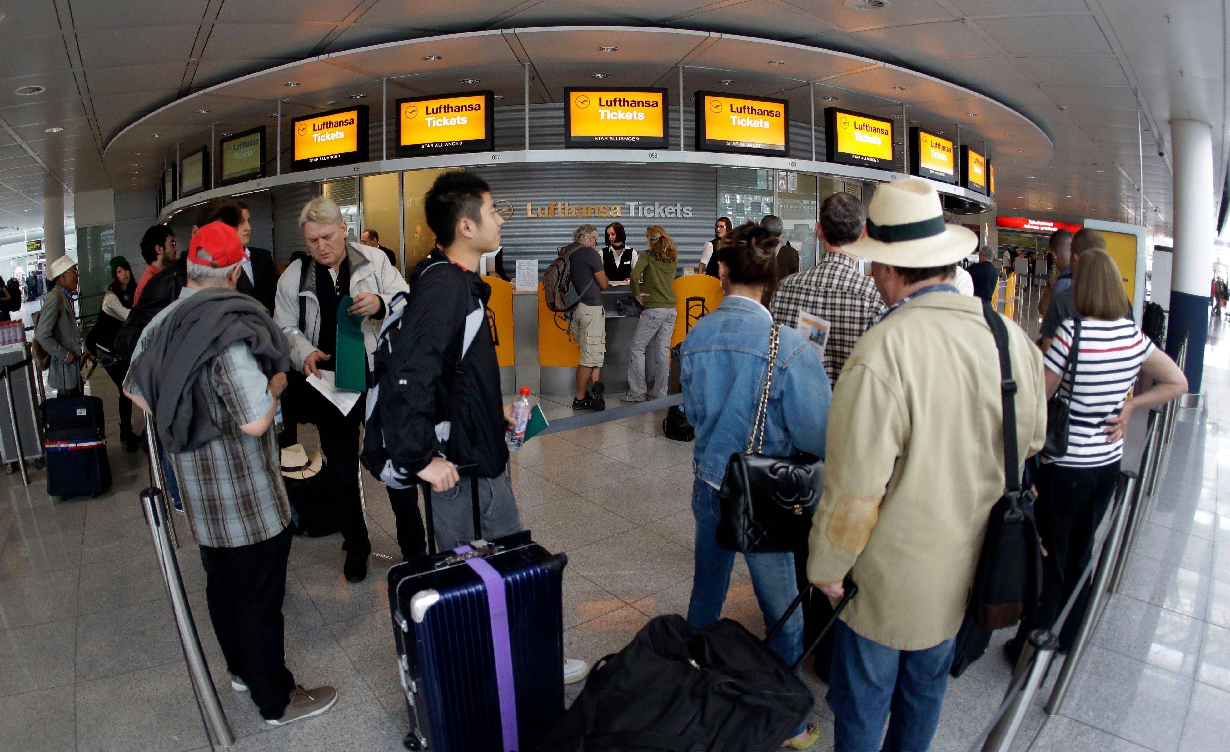 Passengers wait in front of Lufthansa counters as flight attendants of German Lufthansa airline went on an 24-hour-strike for higher wages at the airport in Munich, southern Germany, on Friday, Sept. 7, 2012.