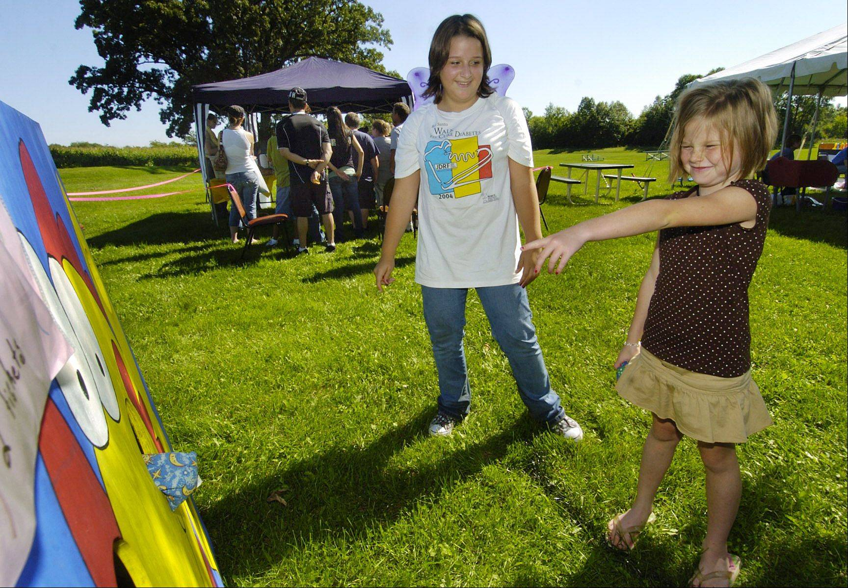 Samantha Stautz, left, watches her cousin Grace Reblin try bean bag toss during the Kids Carnival in Grandwood Park near Gurnee that raises money for the Juvenile Diabetes Research Foundation. Samantha started the carnival in honor of Grace, who has Type 1 diabetes.