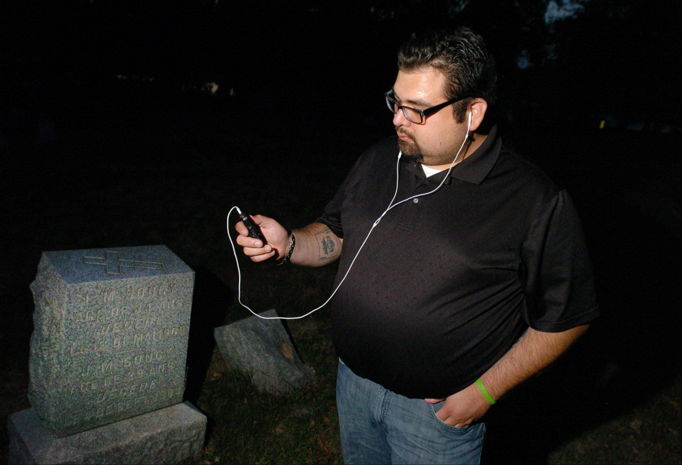 Matthew Herran listens closely to his digital audio recorder after conducting an EVP session at a Montgomery Cemetery. Herran will often spend three or more hours at a location on his hunts.