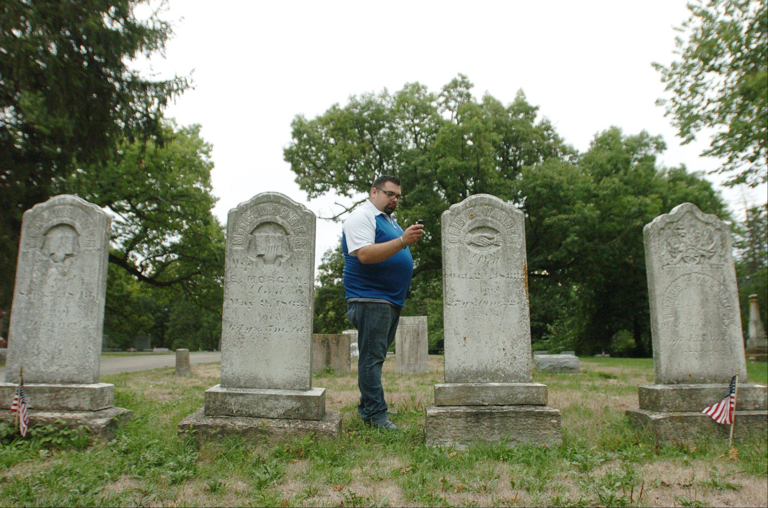 Herran listens for evidence of a spiritual presence in an Oswego cemetery. He also investigates homes.