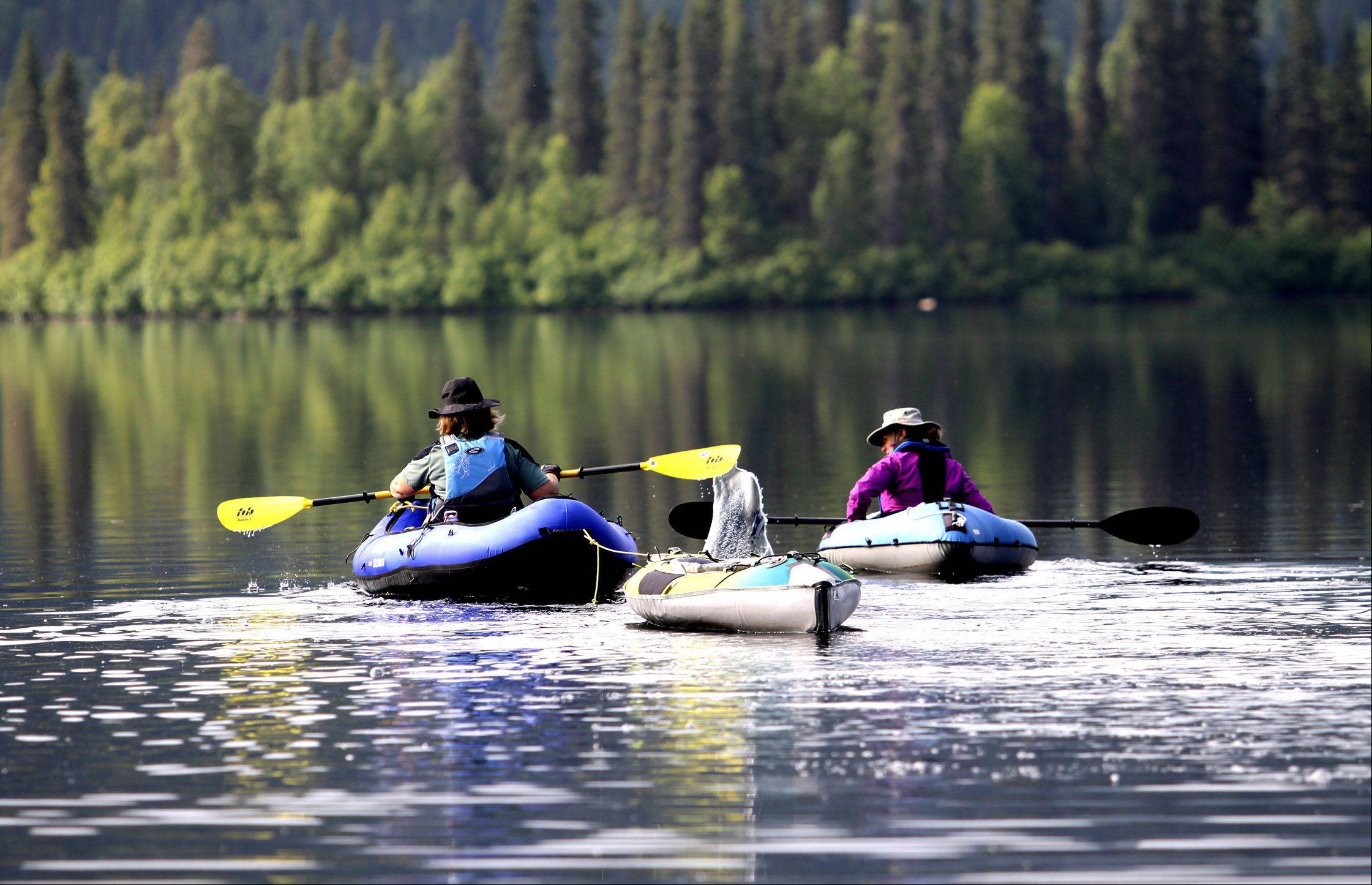 Two people quietly paddle their rafts on tranquil Beir Lake, Alaska in July.