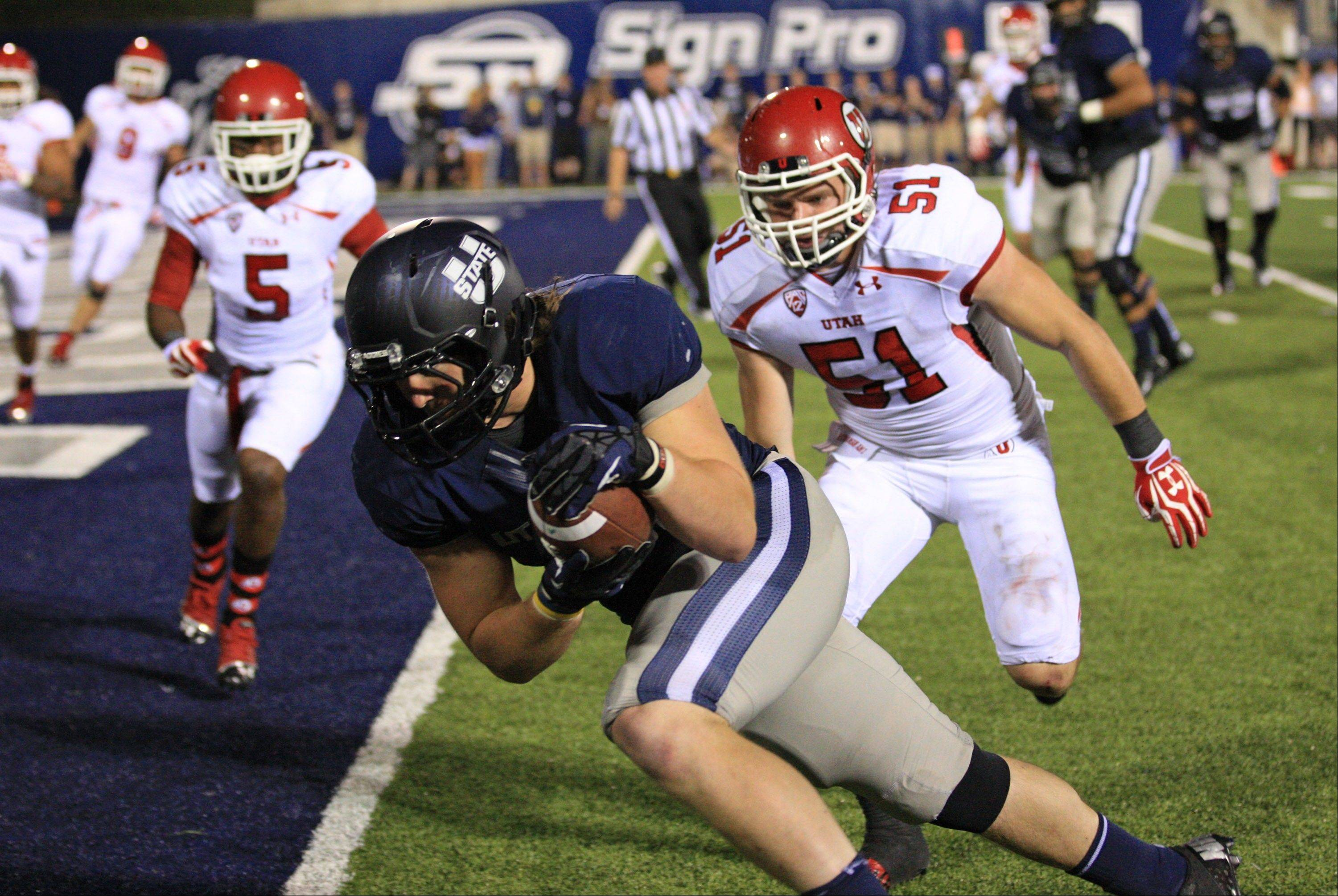 Utah State tight end Kellen Bartlett scores as Utah linebacker Dave Fagergren pursues during the second half Friday in Logan, Utah.