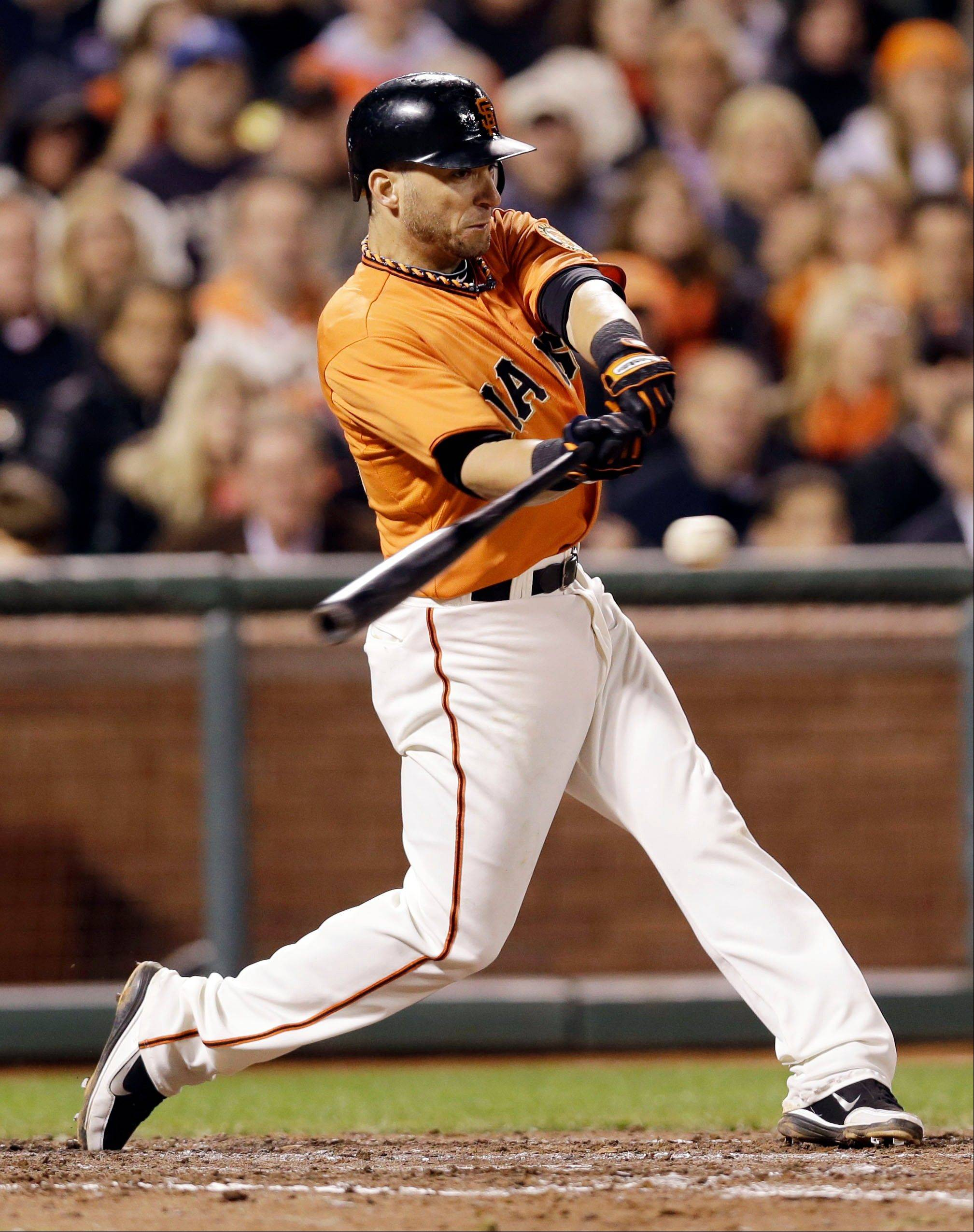 The Giants' Marco Scutaro drives in two runs with a bases-loaded single against the Los Angeles Dodgers during the seventh inning Friday in San Francisco.