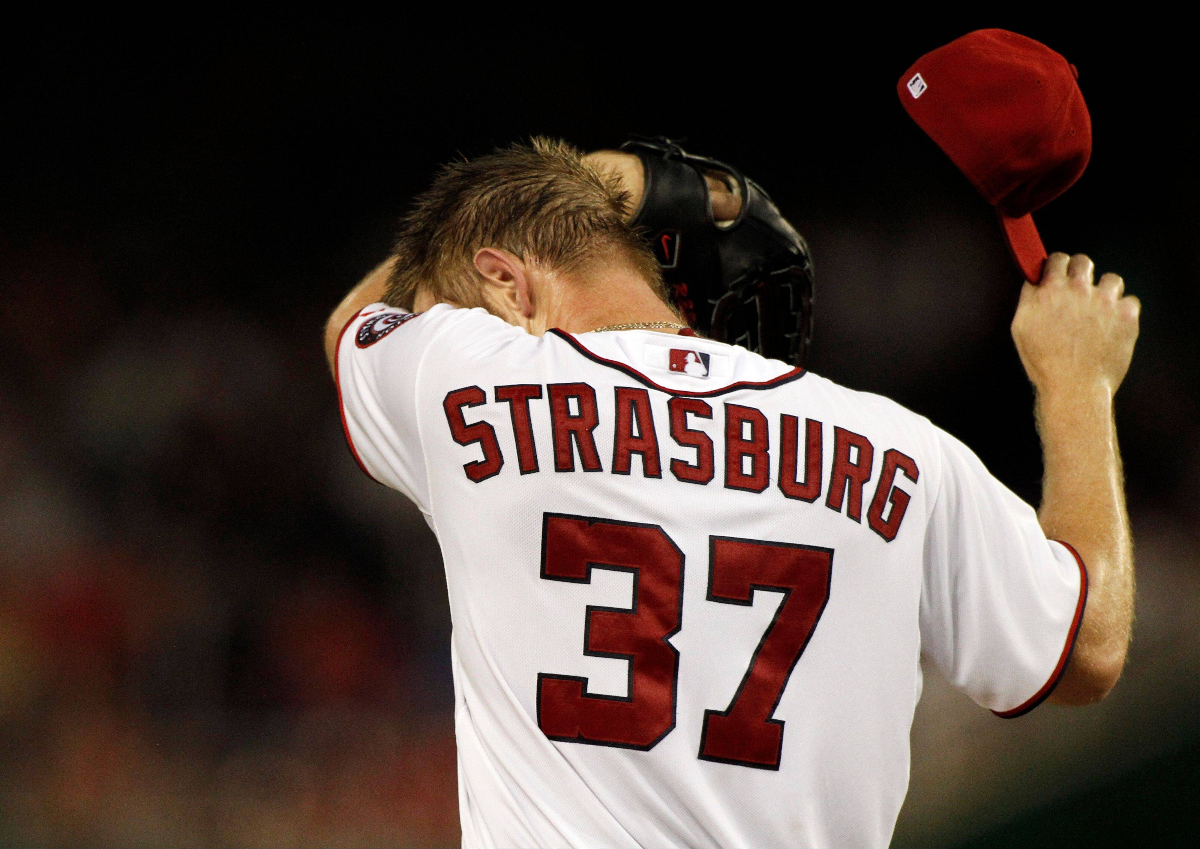 Washington Nationals starting pitcher Stephen Strasburg wipes his face on the mound during the second inning Friday at home against Miami Marlins. Stasburg allowed two runs in the first, one in the second and two in the third, giving up six hits.