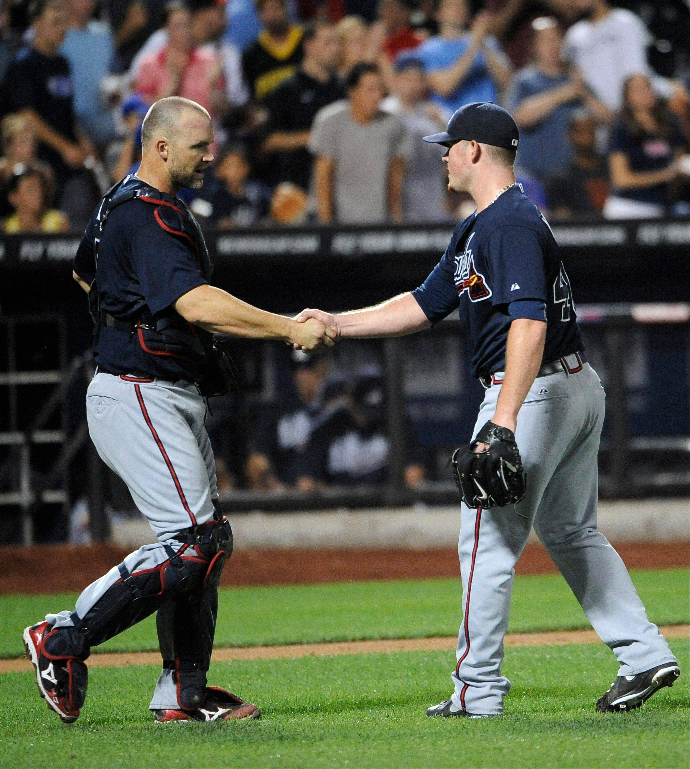Braves catcher David Ross shakes hands with relief pitcher Craig Kimbrel after Atlanta beat the Mets 3-0 Friday in New York.