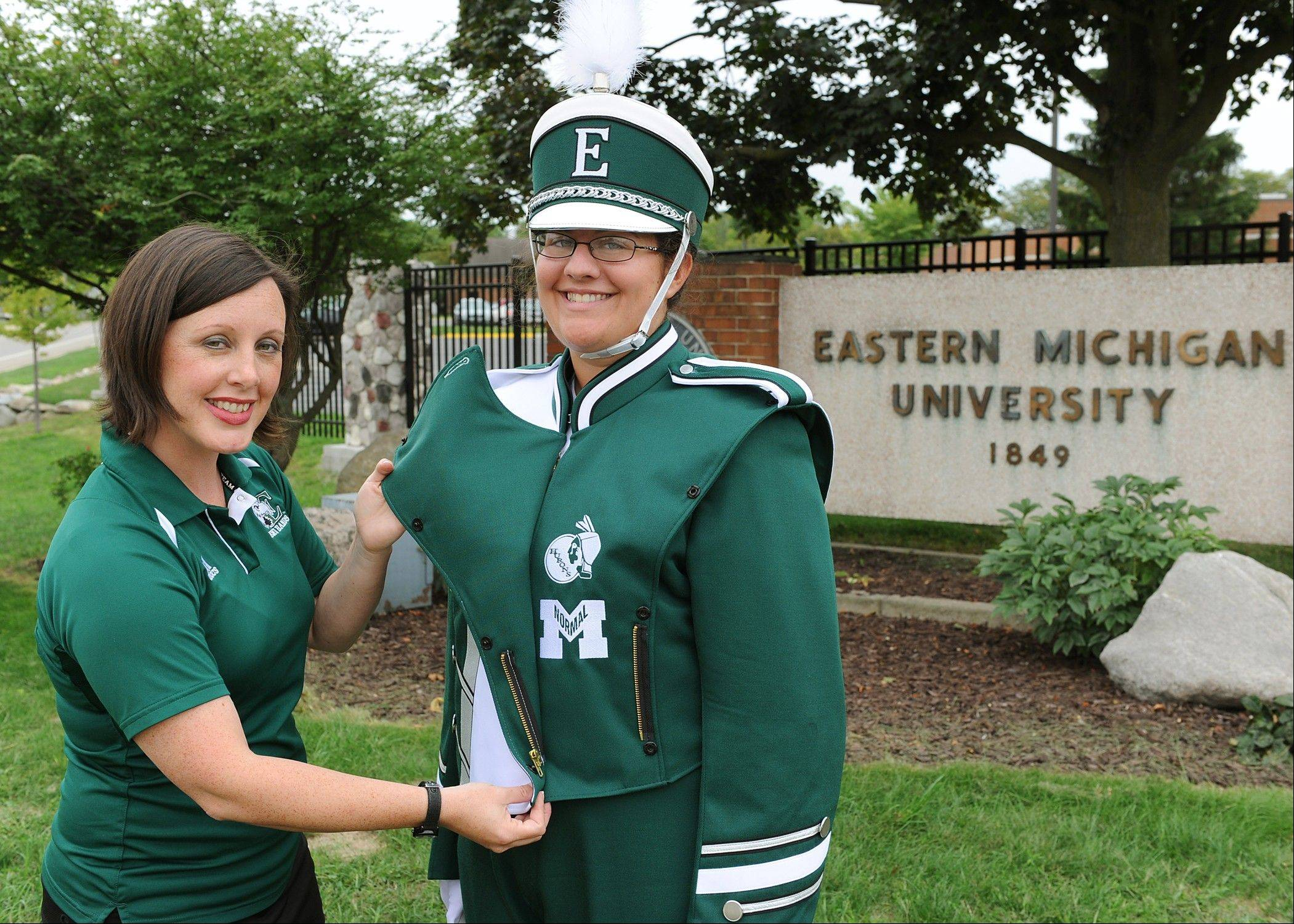 Marching band director Amy Knopps, left, shows off the Huron and Normalite logos embedded in a new marching band uniform worn by uniform manager Maria Eloff.