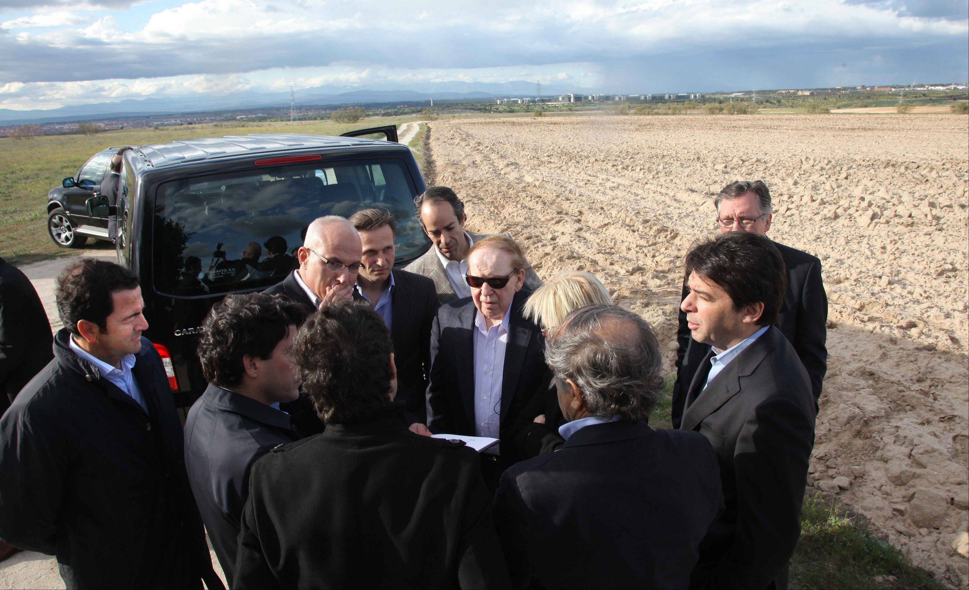 CEO of Las Vegas Sands Corp. Sheldon Adelson, centre with sunglasses, waves while visiting Alcorcon, which was one of the possible sites for the EuroVegas project on the outskirts of Madrid, with others unidentified.
