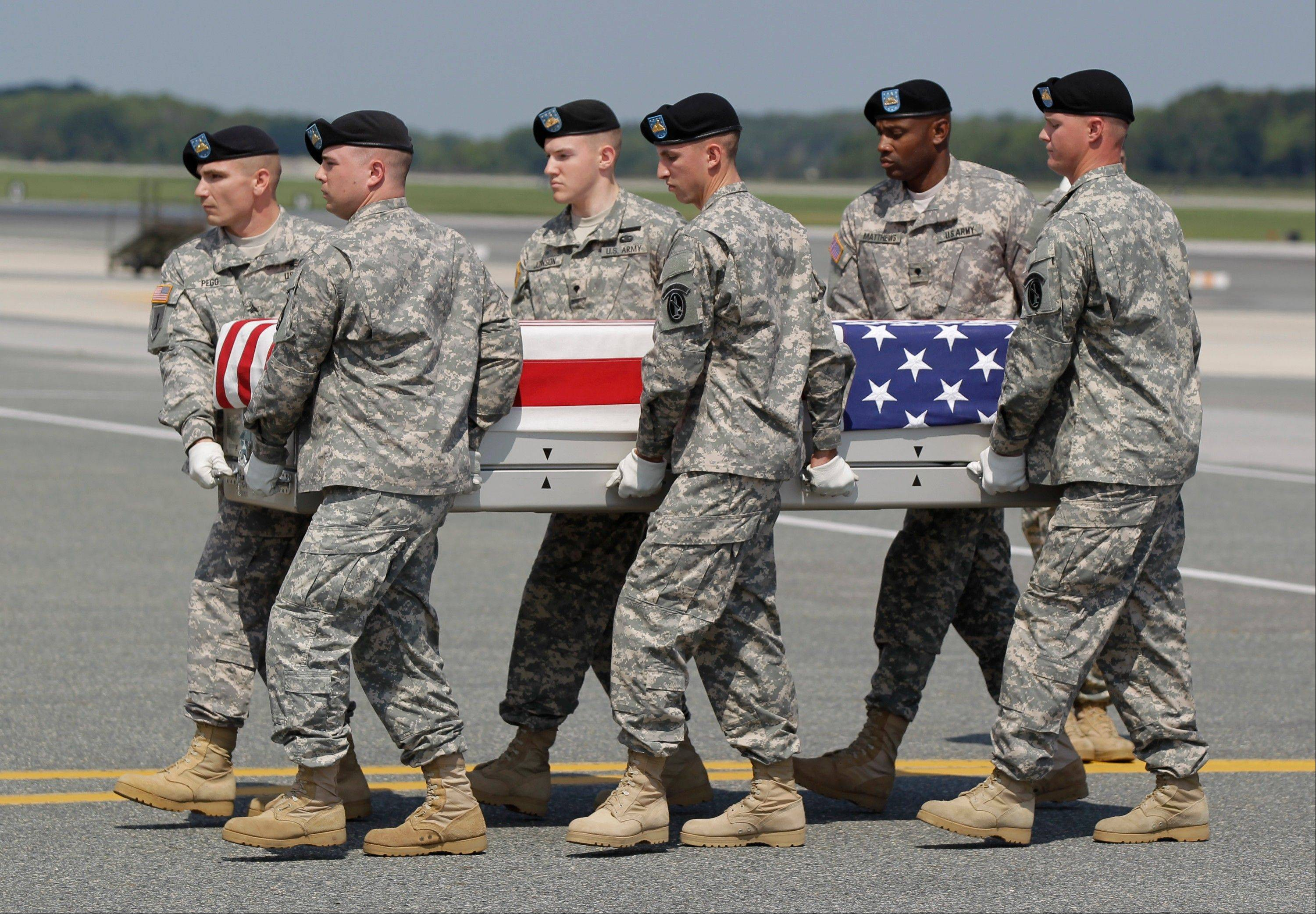 Associated Press/Aug. 30 An Army carry team moves a transfer case containing the remains of Pfc. Shane W. Cantu of Corunna, Mich., at Dover Air Force Base, Del.
