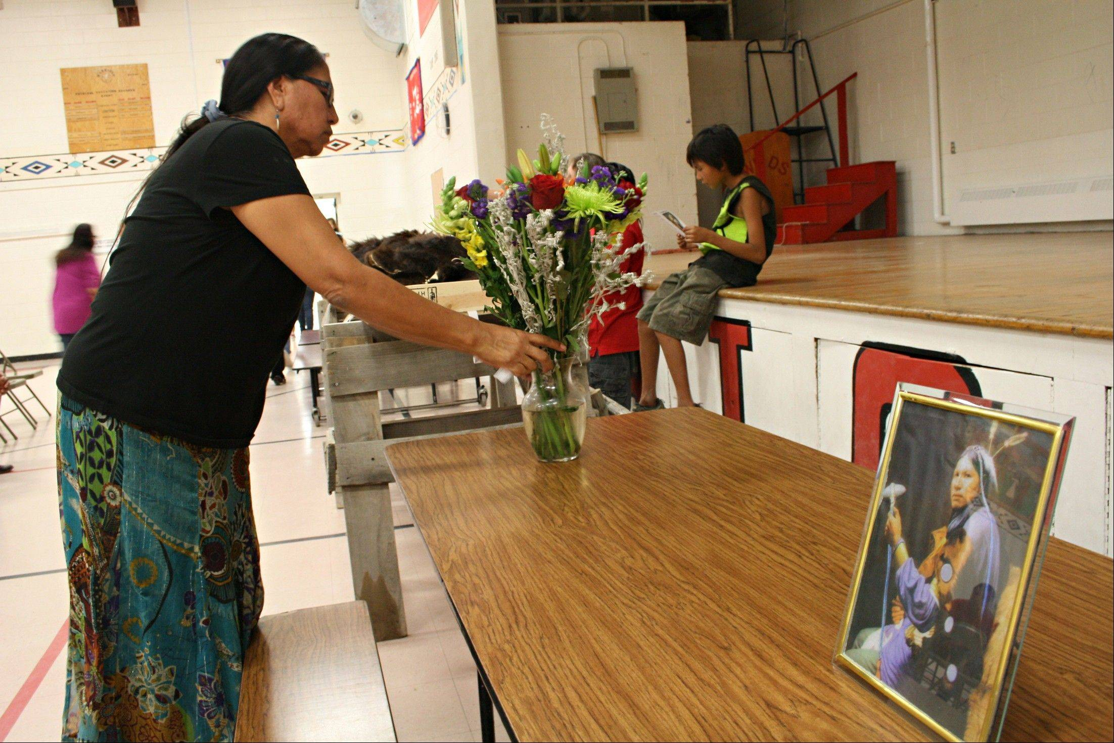 A woman places flowers Saturday next to a photo of Albert Afraid of Hawk at his wake service in Manderson, S.D. Afraid of Hawk, a member of the Oglala Sioux Tribe, died 112 years ago while performing with Buffalo Bill's Wild West show.