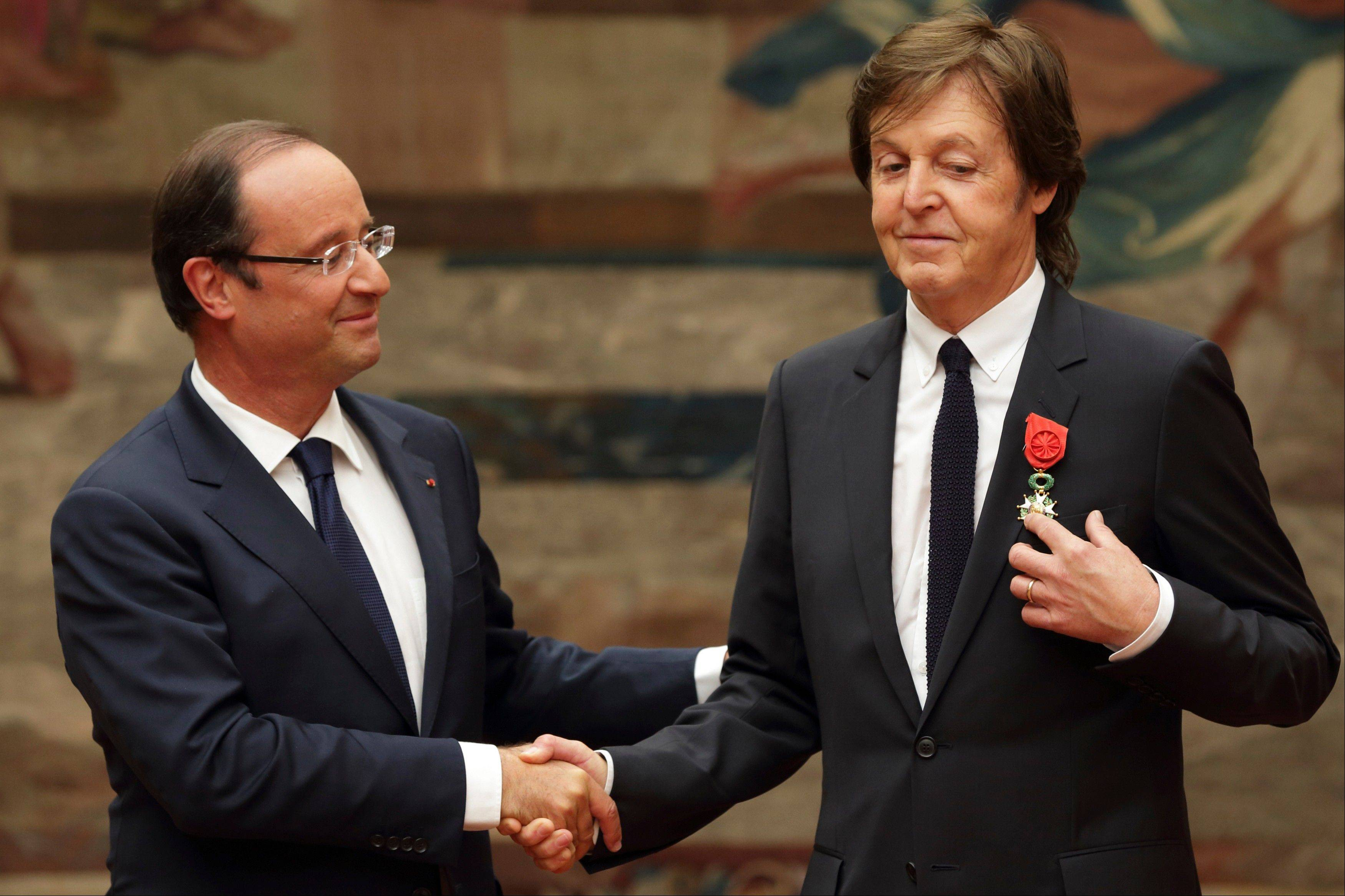 French President Francois Hollande, left, awards British musician Paul McCartney during a decoration ceremony photo session Saturday at the Elysee Palace in Paris.