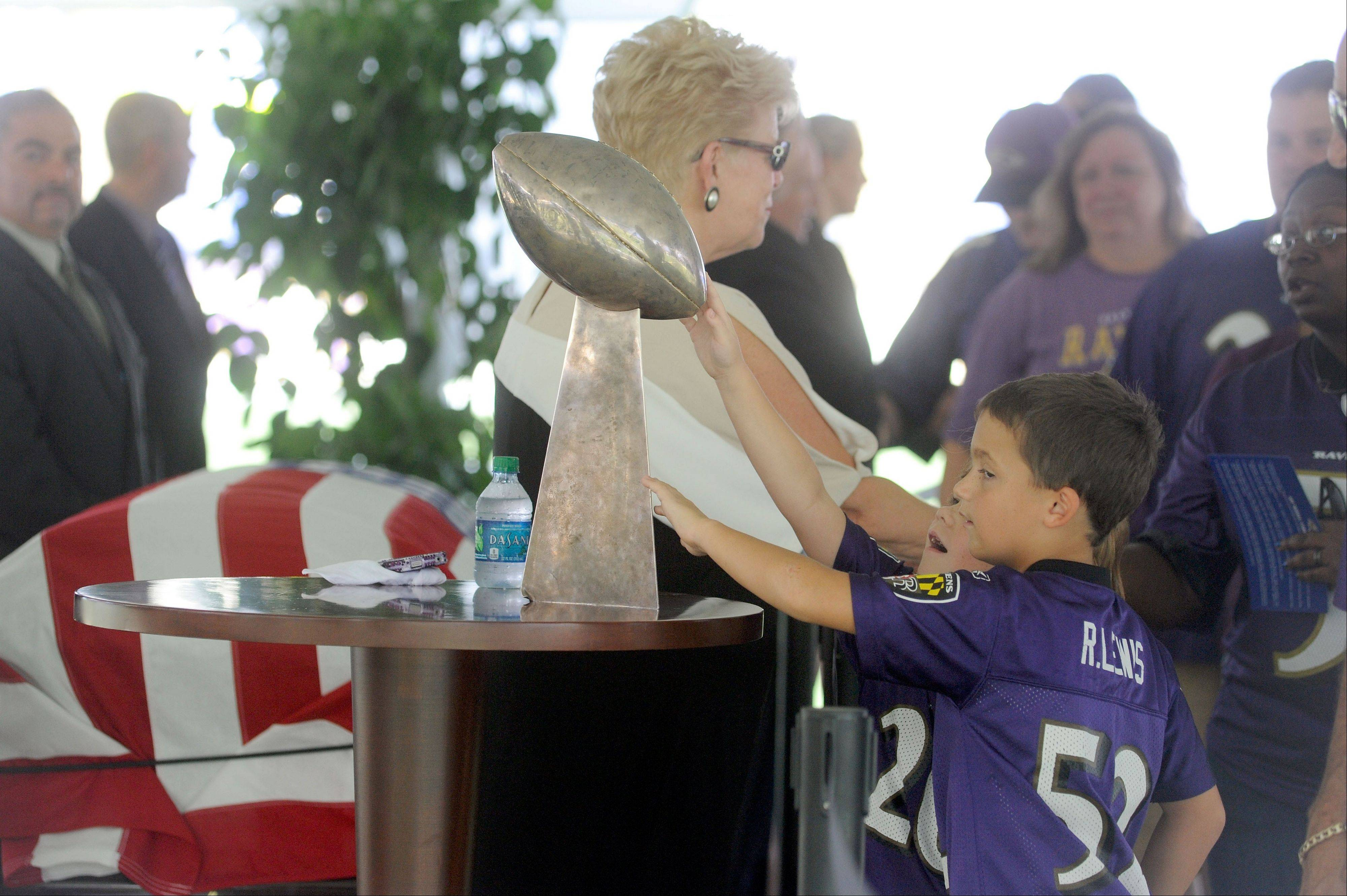 Children touch the Baltimore Ravens' Vince Lombardi Trophy from the team's 2001 Super Bowl championship during a public viewing Saturday of the casket of former Ravens owner Art Modell at M&T Bank Stadium in Baltimore.