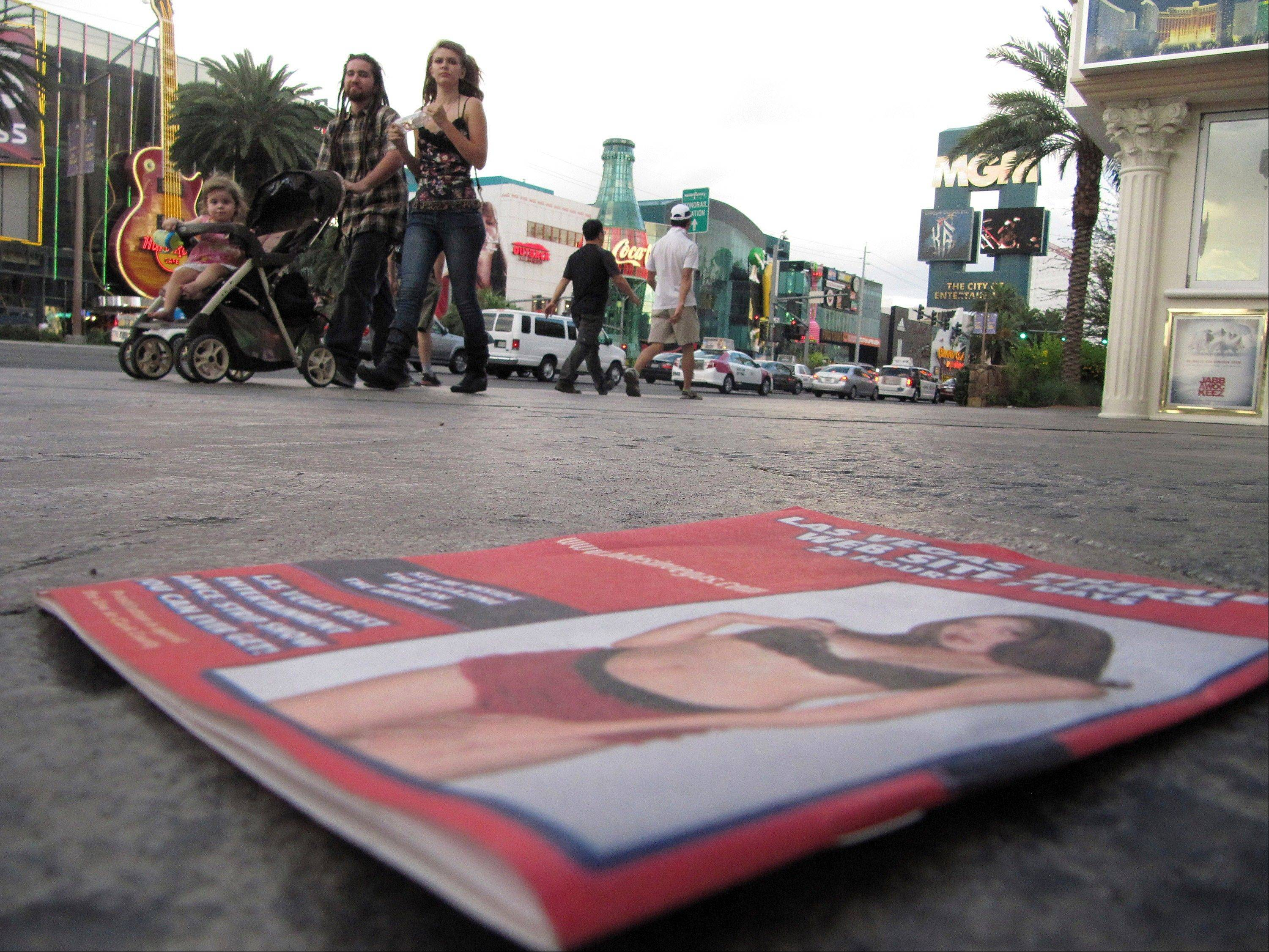 An unidentified couple on a Las Vegas Strip sidewalk push a toddler in a stroller Wednesday past a discarded pamphlet advertising exotic dancers.