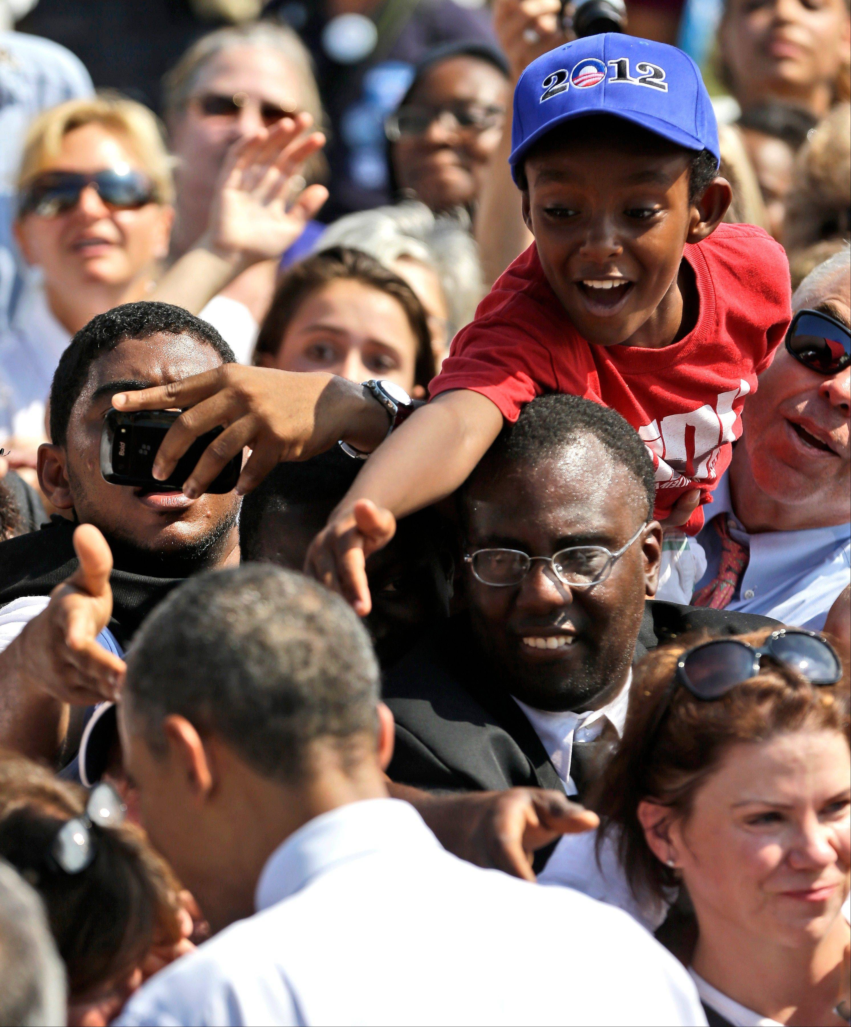 A young supporter reaches out in an attempt to greet President Barack Obama Friday during a campaign event at Strawbery Banke Museum in Portsmouth, N.H.