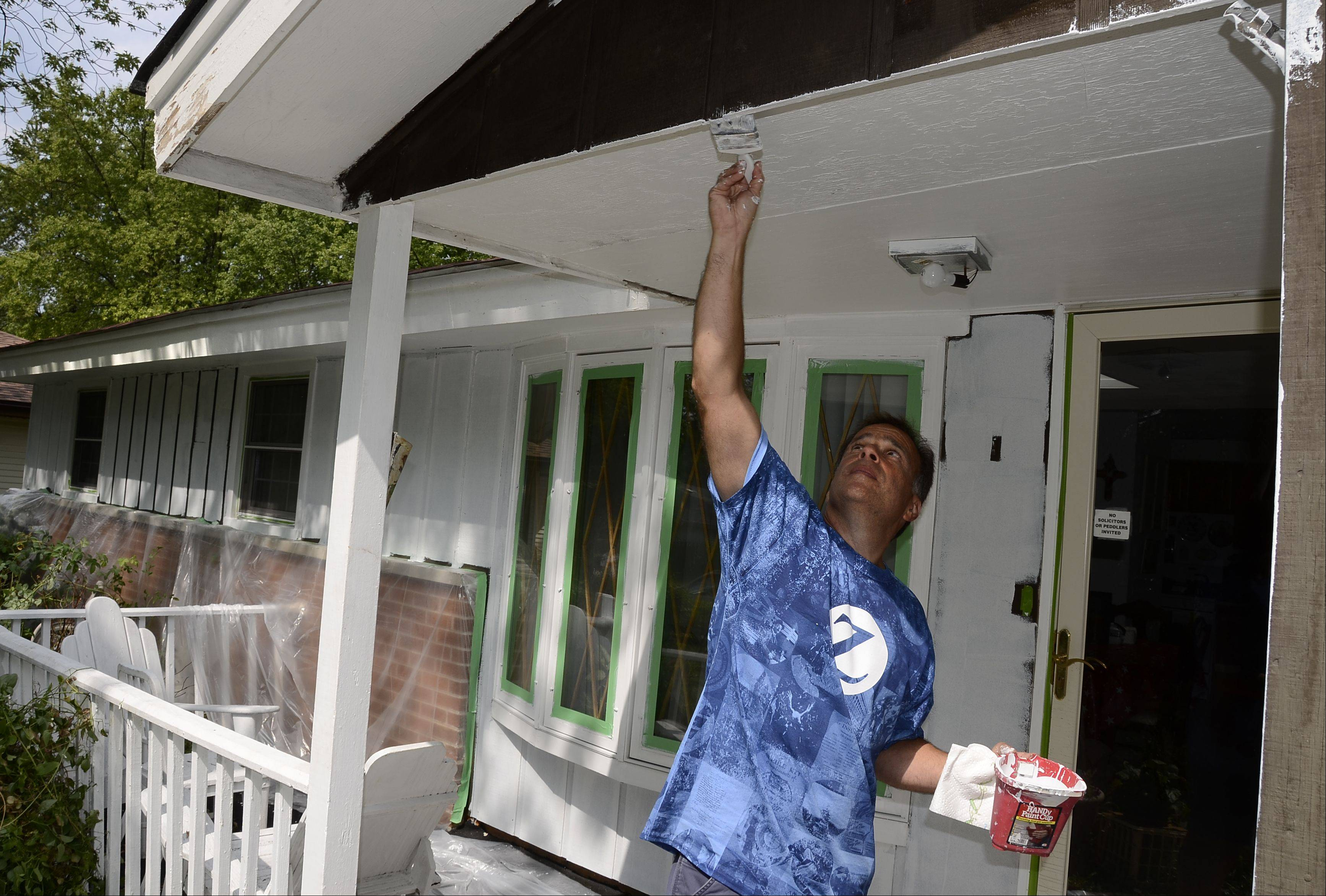 Mark Puccio, a resident of Hoffman Estates and a member of Team Zurich, helps paint Alice Barmann's house Friday in Schaumburg as part of the Habitat for Hummanity 25th Community Paint-a-thon.