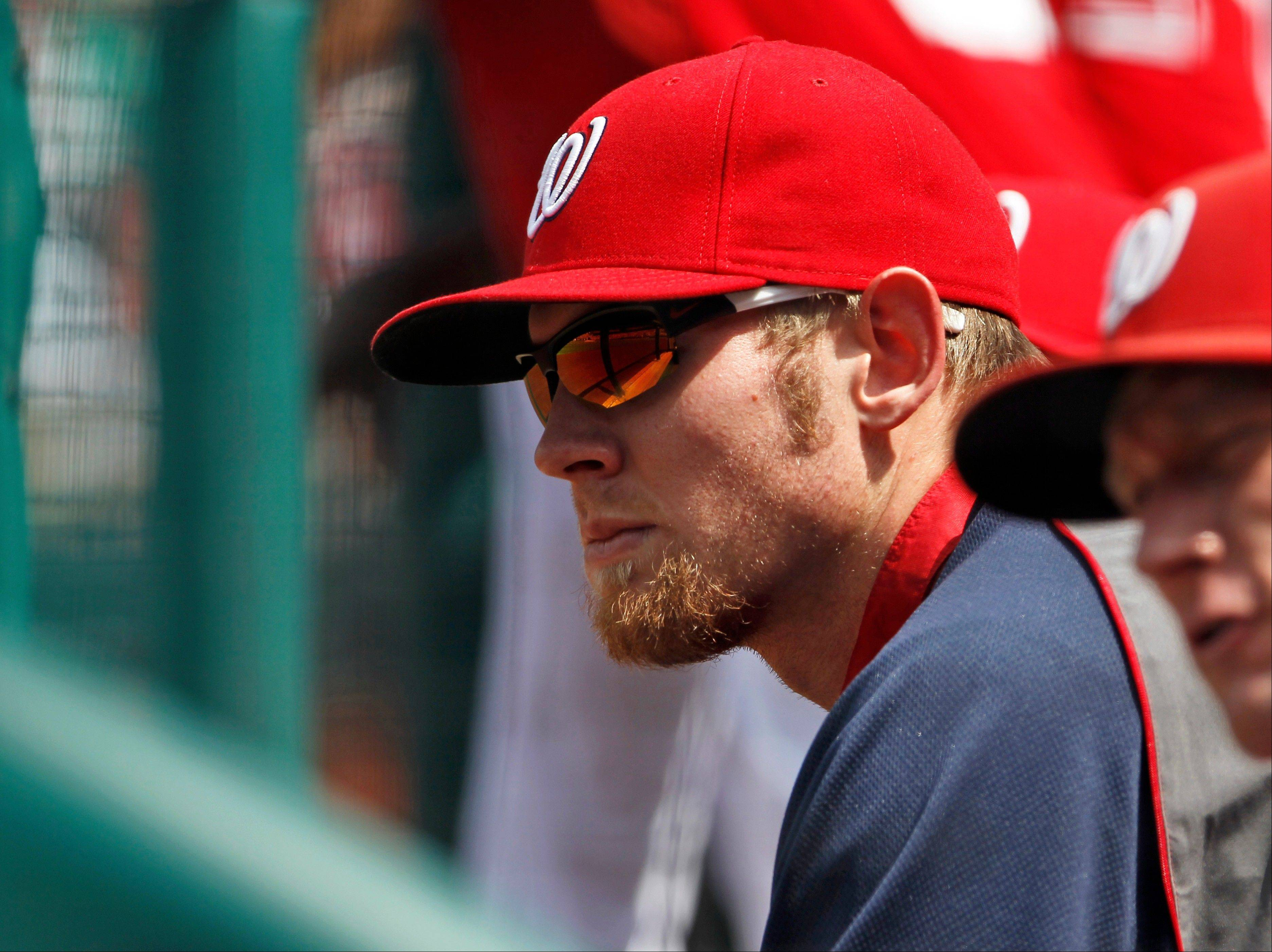 Washington Nationals pitcher Stephen Strasburg sits in the dugout Saturday during the first inning of a baseball game against the Miami Marlins at Nationals Park. Strasburg's season is over after the Washington Nationals decided to shut down the ace right-hander following a shaky start against the Miami Marlins. Manager Davey Johnson made the announcement Saturday morning.