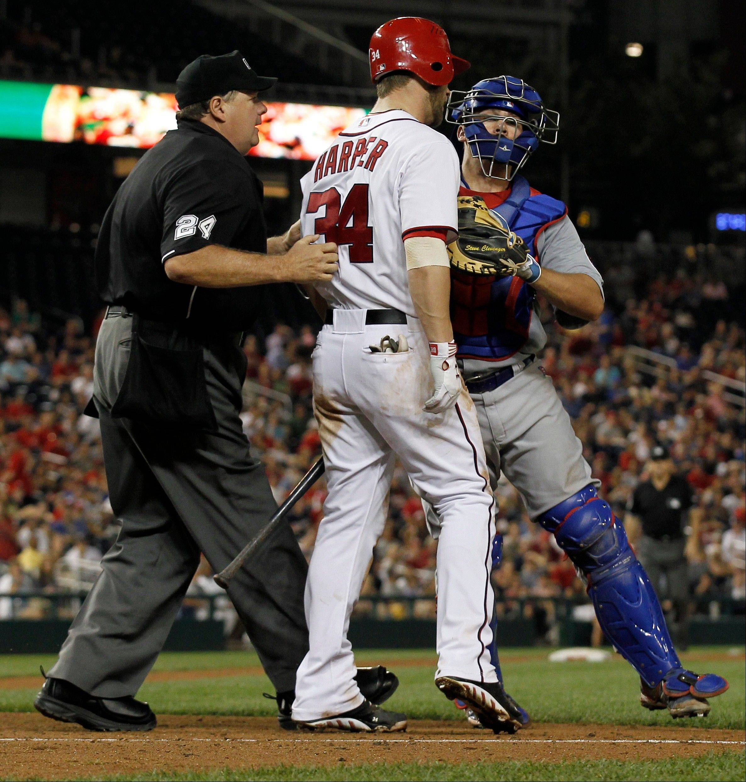The Nationals' batter Bryce Harper (34) is restrained by home plate umpire Jerry Lane, left, and Cubs catcher Steve Clevenger after an inside pitch during the sixth inning Thursday in Washington. The benches and bullpens emptied onto the field.