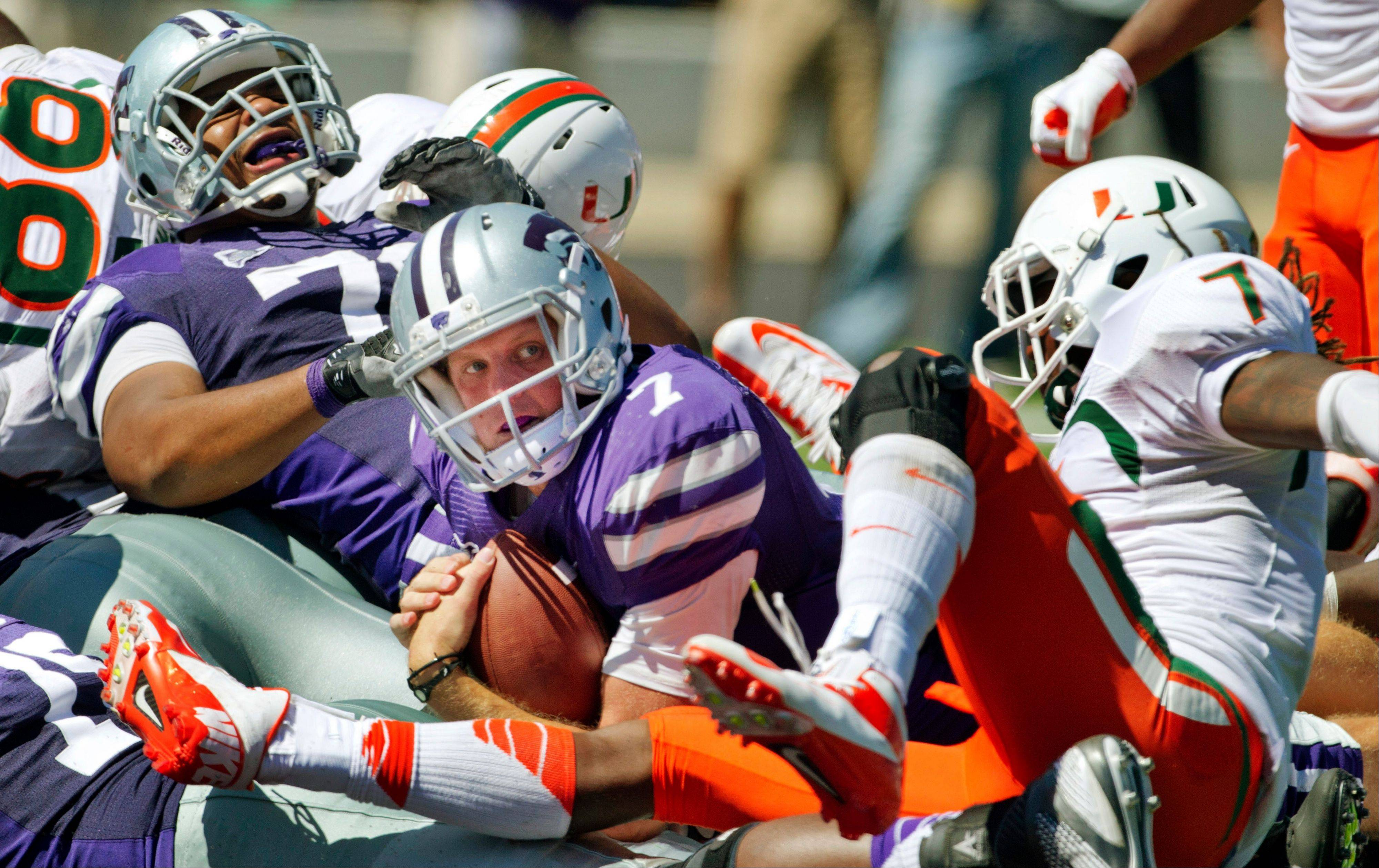 Kansas State quarterback Collin Klein looks for an official's call after crossing the goal line past Miami defensive back Vaughn Telemaque during the second half Saturday in Manhattan, Kan.
