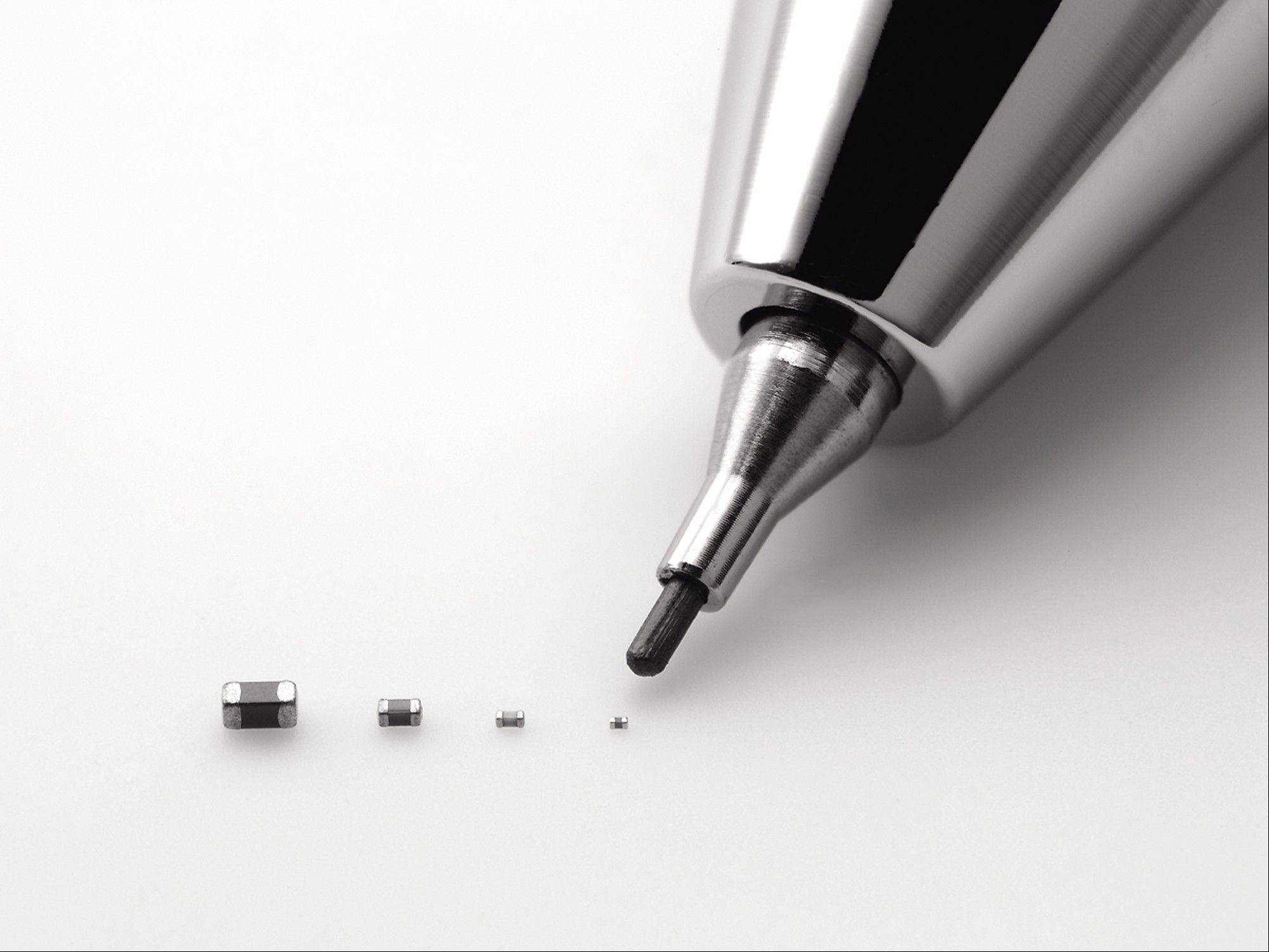 Murata's latest capacitor measures just 0.25 millimeter by 0.125 millimeter, right, is pointed by a mechanical pencil as it is displayed with its bigger size models. Small is big for Murata: The Japanese electronics maker has developed the world's tiniest component known as the capacitor. And that's big business. Capacitors, which store electric energy, are used in the dozens, even in the hundreds, in just about every type of gadget - smartphones, laptops, hybrid cars, medical equipment and digital cameras.