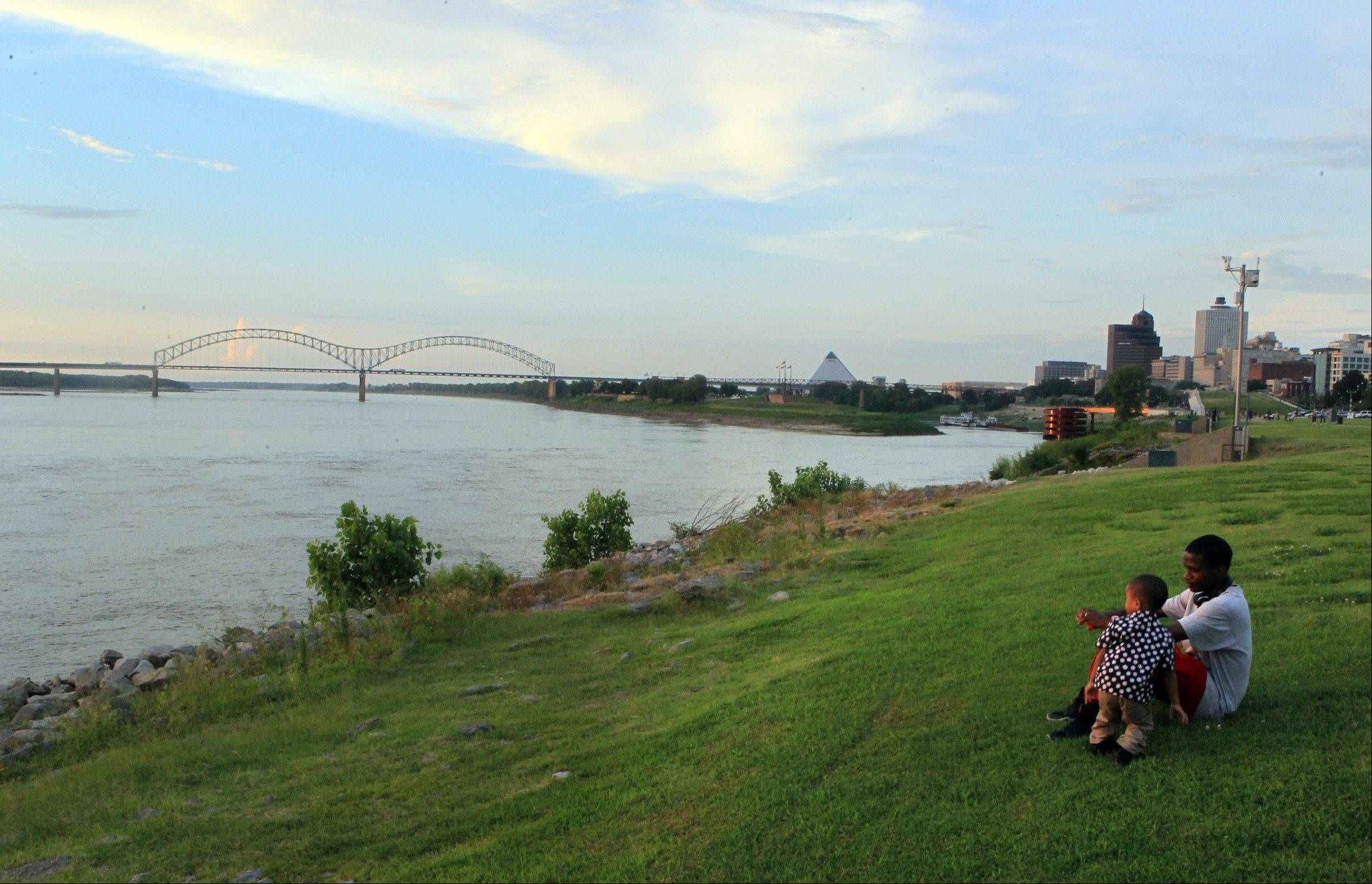 Marcus Milam, right, and his son Markes Milam, 3, sit along the banks of the Mississippi River in Tom Lee Park in Memphis, Tenn.