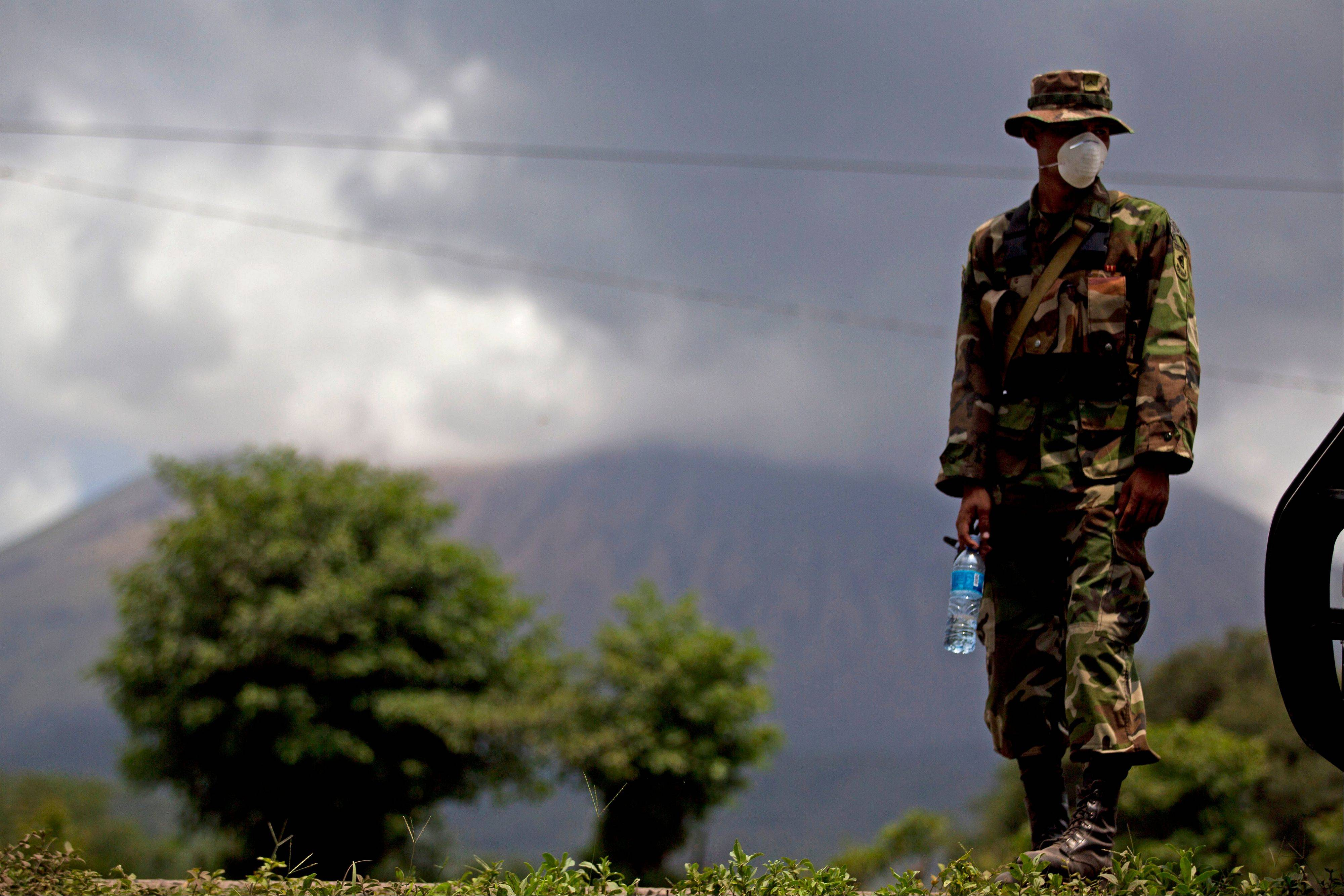 A Nicaraguan soldier wears a protective mask Saturday as the San Cristobal volcano, in background, spews smoke and ash, near Chinandega, Nicaragua.