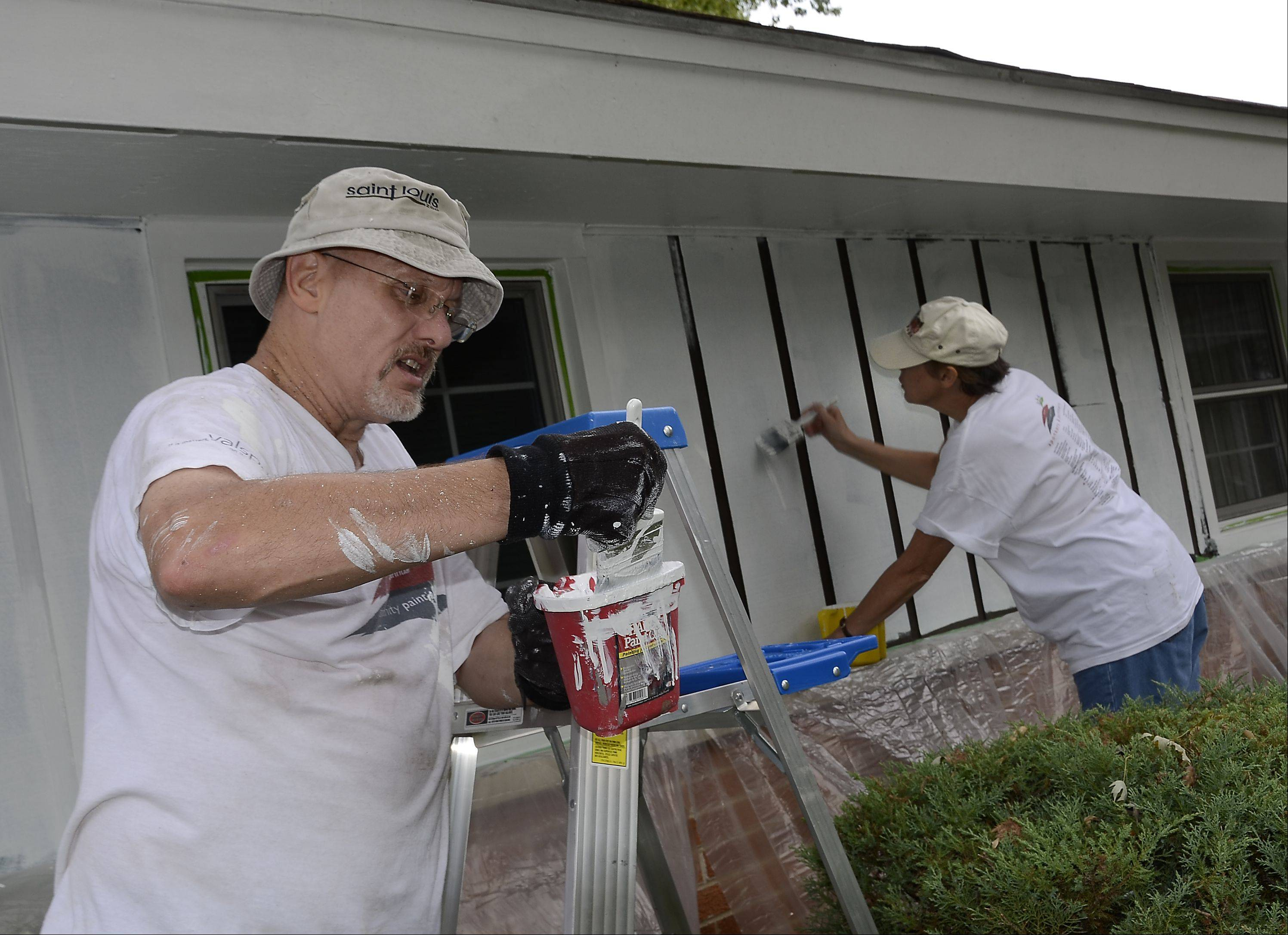 Husband and wife Steve and Nancy Middleton of Team Zurich paint Alice Barmann's house on Friday. Nancy works for Zurich Insurance, which formed a team of volunteers for the Community Paint-a-thon.