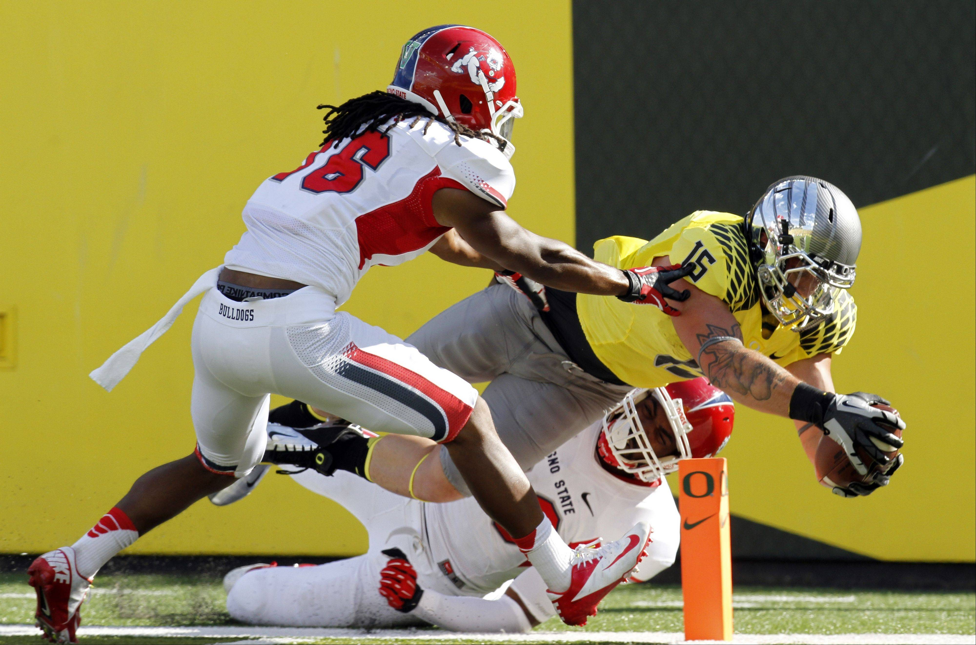 Oregon tight end Colt Lyerla dives in for a touchdown against Fresno State defenders Phillip Thomas, left, and Tristan Okpalaugo during the first half Saturday in Eugene, Ore.