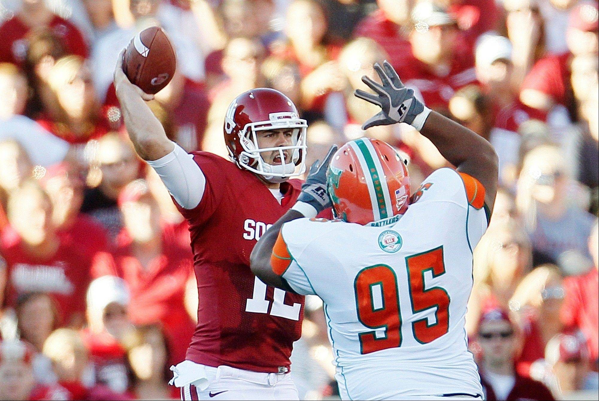 Oklahoma quarterback Landry Jones passes under pressure from Florida A&M defensive tackle Padric Scott during the first quarter Saturday in Norman, Okla.