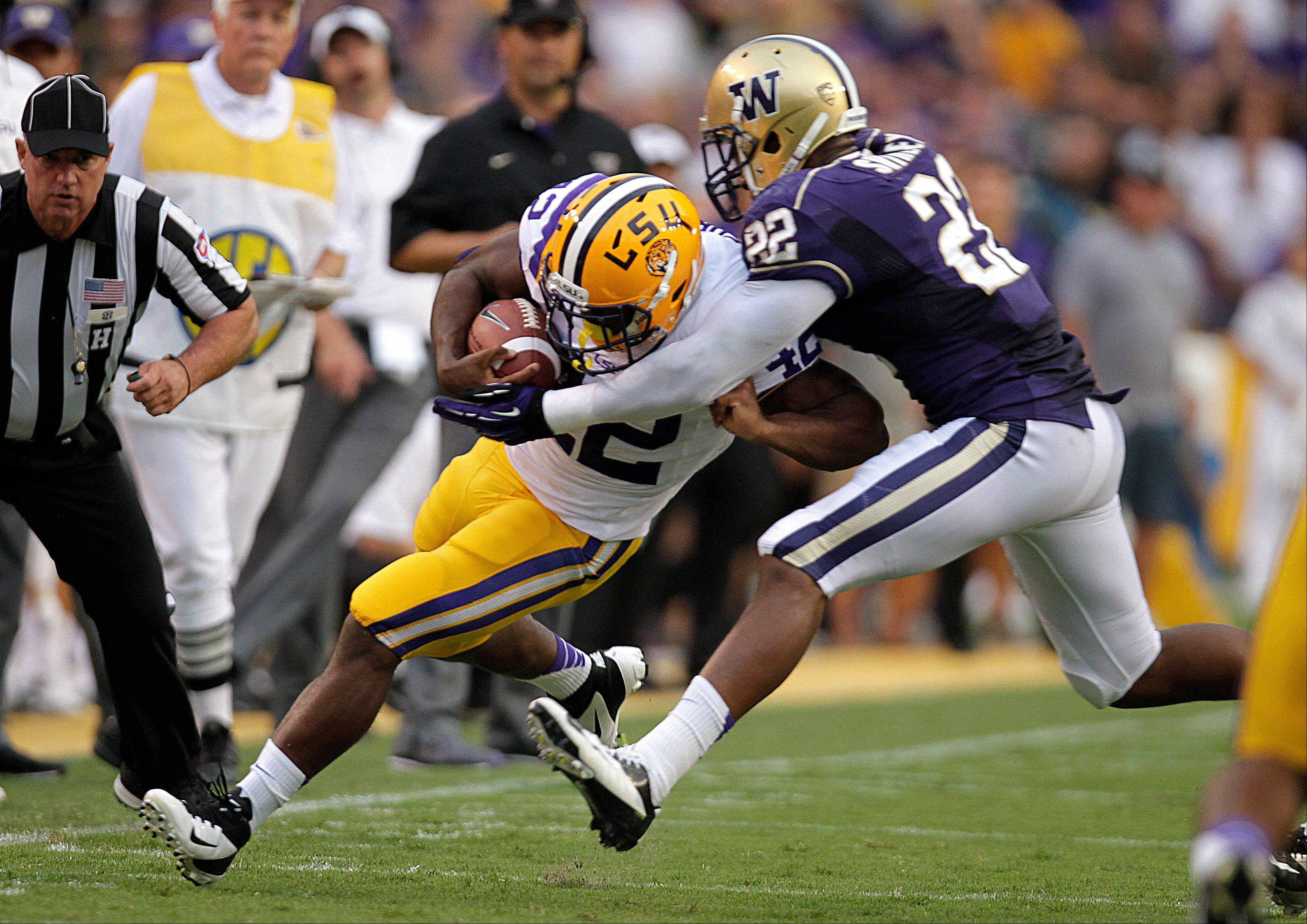 LSU running back Michael Ford tries to break a tackle by Washington defensive end Josh Shirley during the first half Saturday in Baton Rouge, La.