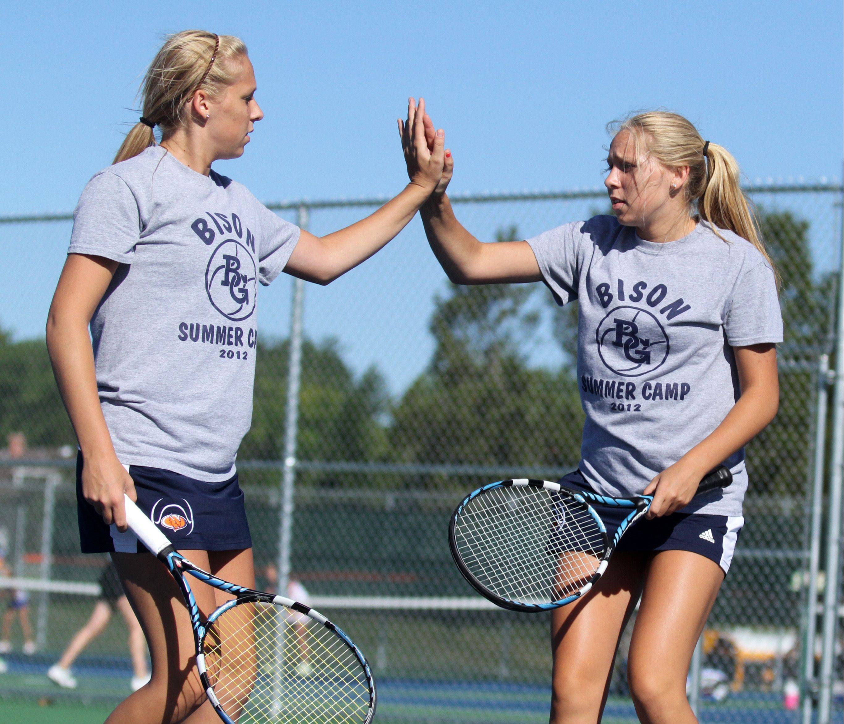 Buffalo Grove High School twins Dana Goggin, foreground, and Lauren celebrate a point in doubles against Lake Zurich's Melanie Spears and Sam Wilson at Buffalo Grove High School girls tennis invitational on Saturday, September 8.