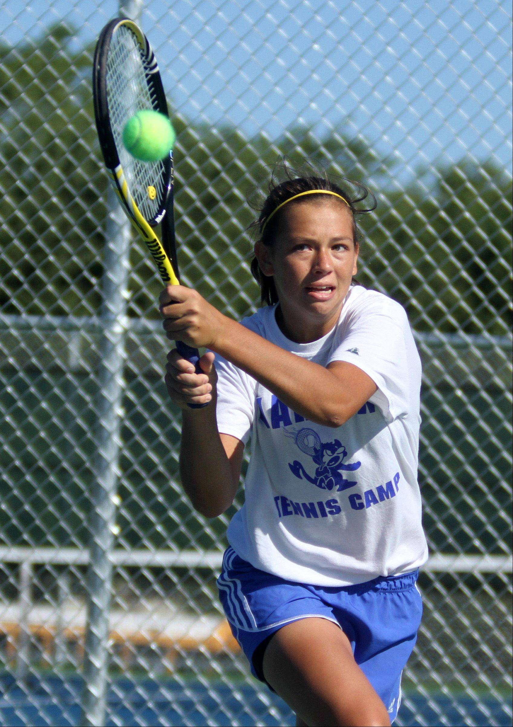 Warren Township High School's Micayla Schultz charges the ball in doubles with teammate Courtney Sunday against Libertyville at Buffalo Grove High School girls tennis invitational on Saturday, September 8.
