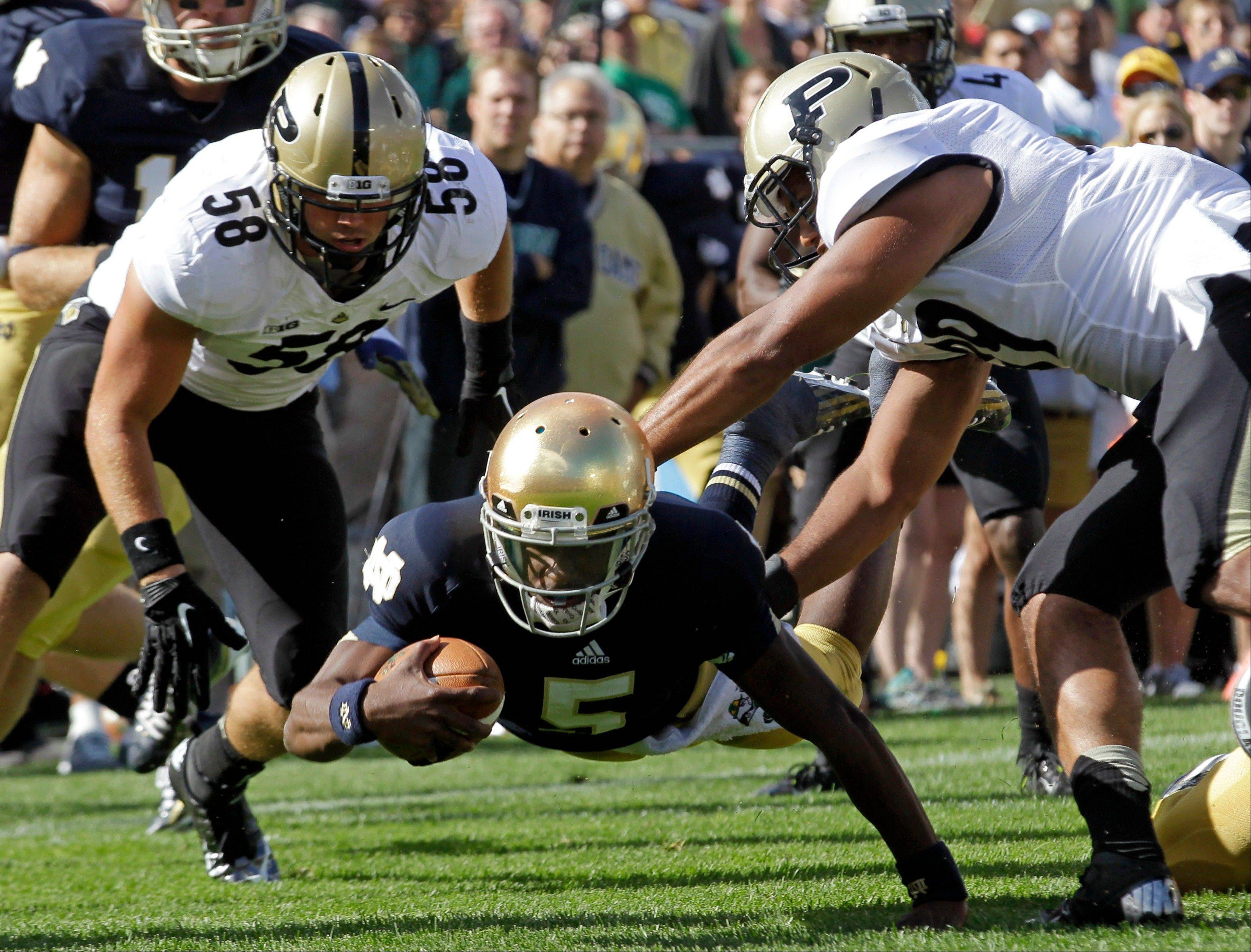 Notre Dame quarterback Everett Golson, center, attempts to dive into the end zone between Purdue defensive end Robert Maci (58) and linebacker Joe Gilliam during the first half of an NCAA college football game in South Bend, Ind., Saturday.