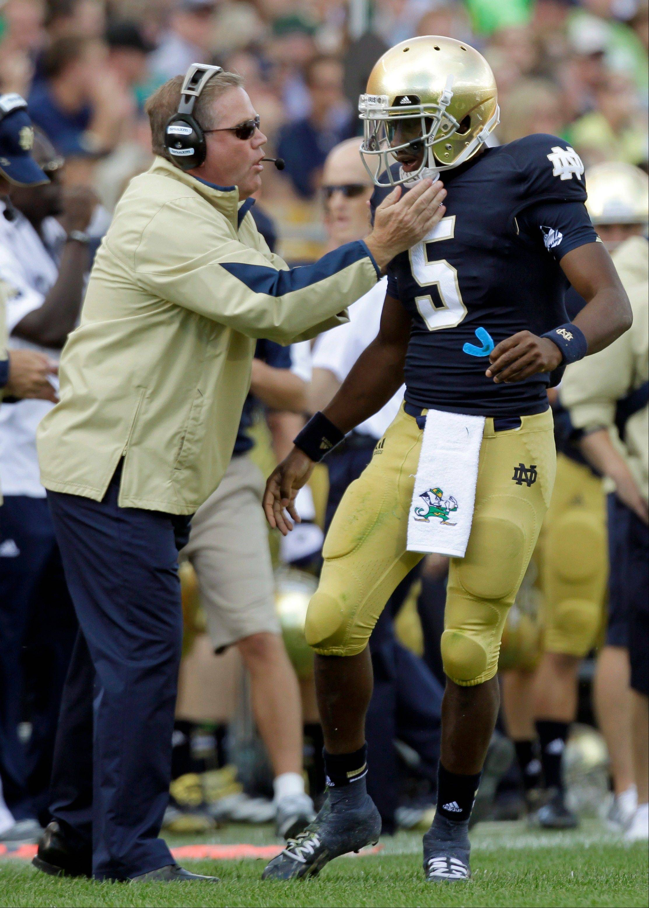 Notre Dame coach Brian Kelly, left, gives a play to quarterback Everett Golson during the first half of an NCAA college football game against Purdue in South Bend, Ind., Saturday.