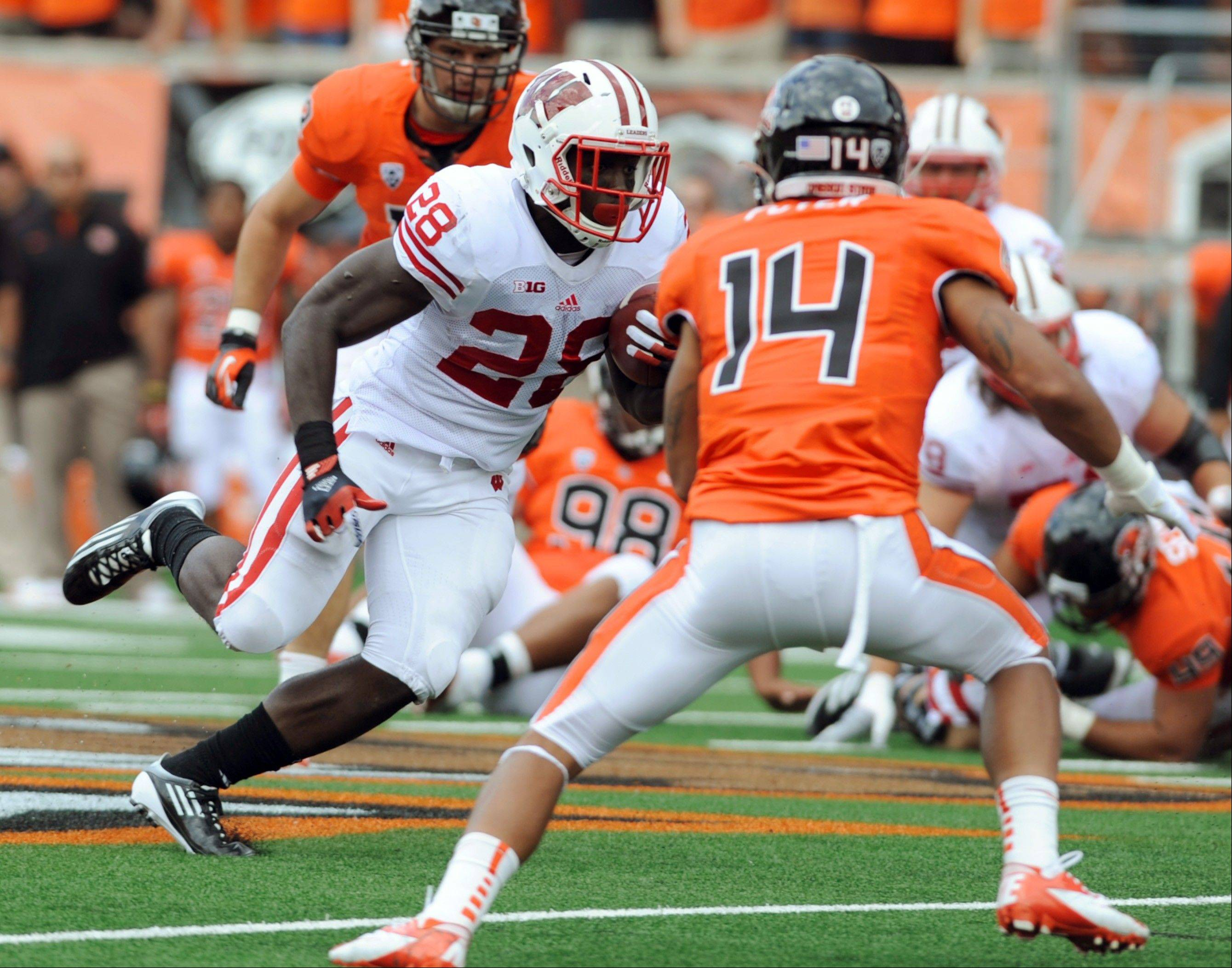 Oregon State's Jordan Poyer (14) rushes against Wisconsin's Montee Ball (28) during the first half of their NCAA college football game in Corvallis, Ore., Saturday.