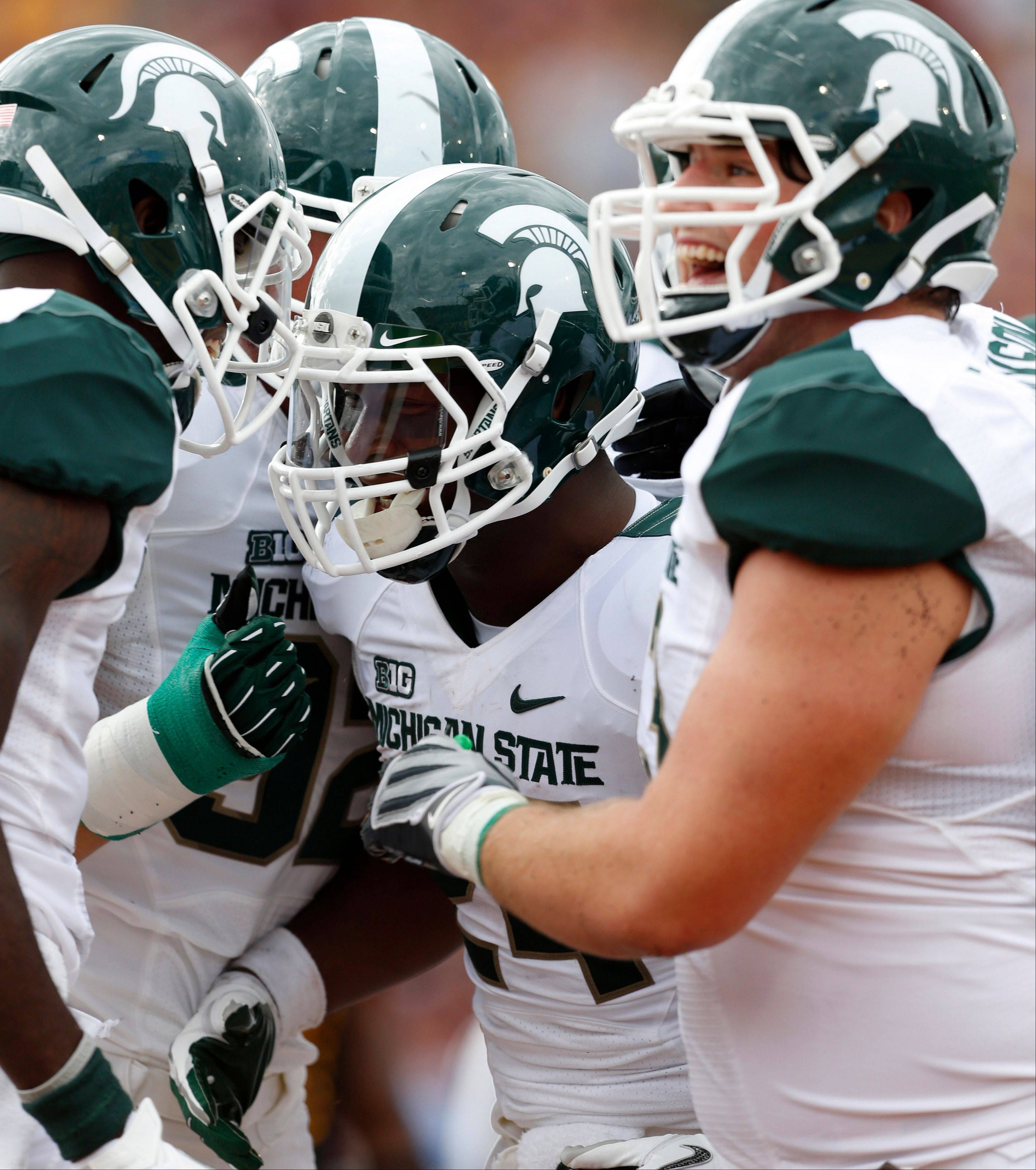 Michigan State's Le'Veon Bell, center, celebrates his second-quarter touchdown with teammates Saturday on the road against Central Michigan.