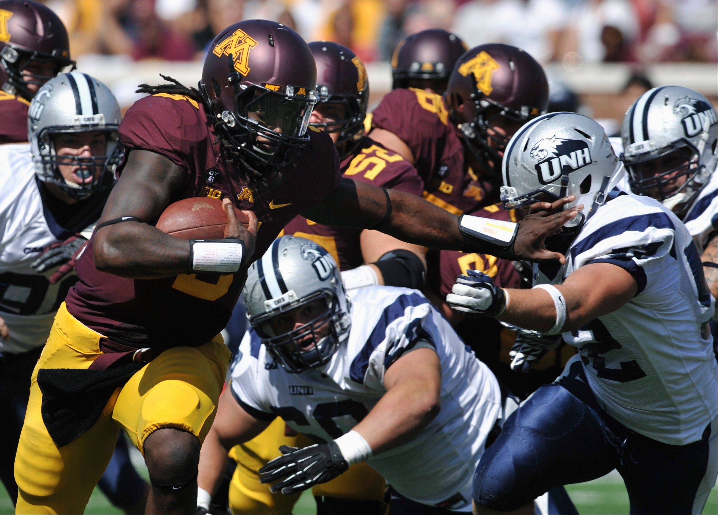 Minnesota quarterback MarQueis Gray, left, gives New Hampshire's Matt Evans a stiff-arm on a touchdown run during the second quarter Saturday in Minneapolis.