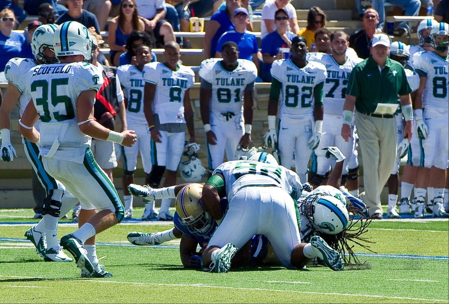 Tulane's Devon Walker (18), right, and Julius Warmsley (92) tackle Tulsa's Kenny Welcome, bottom left, during Saturday's game in Tulsa, Okla. Walker was seriously hurt on this play.