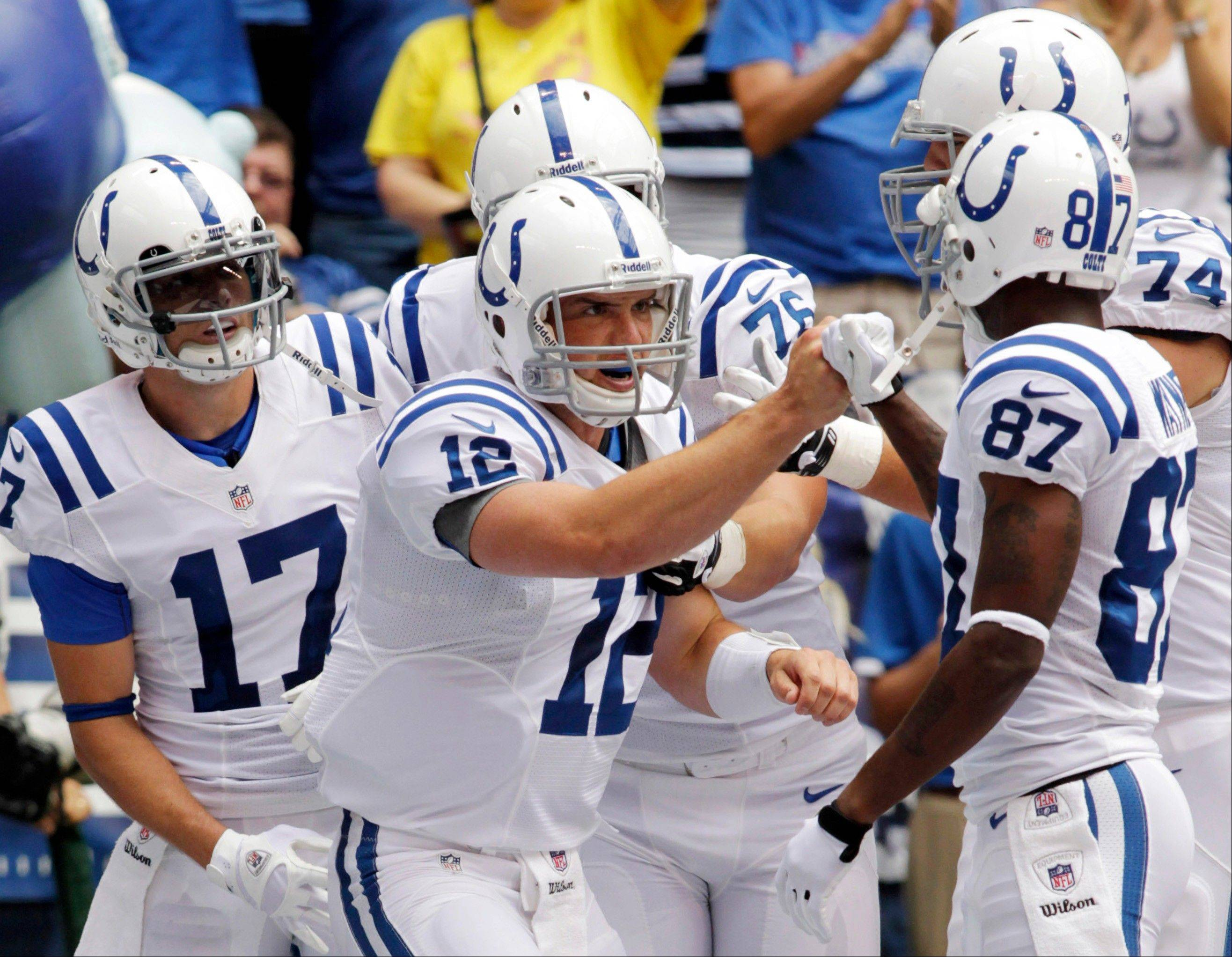 Indianapolis Colts quarterback Andrew Luck (12) celebrates with wide receiver Reggie Wayne (87) after he threw a touchdown pass to wide receiver Austin Collie (17) during a preseason game against the St. Louis Rams. Luck opens the regular season Sunday against the Bears at Soldier Field.