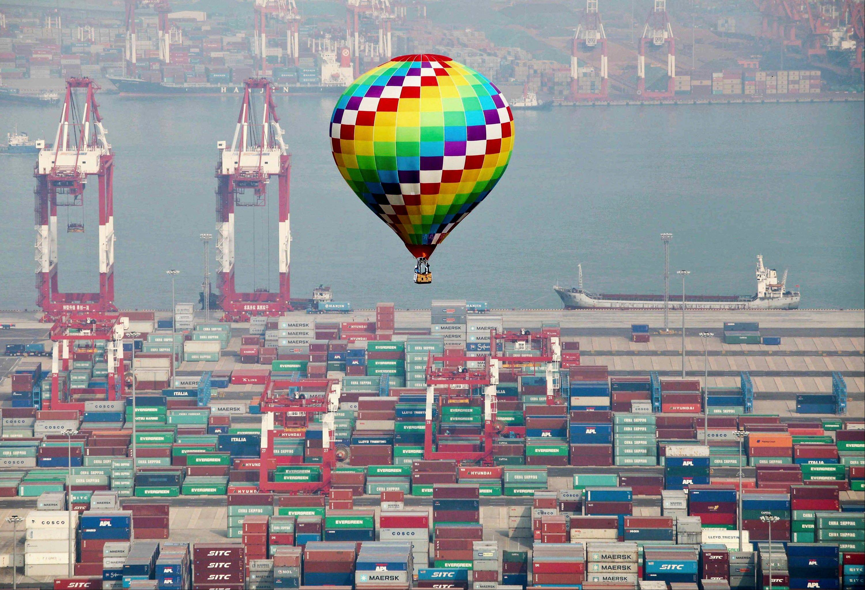 A hot-air balloon flies over a container port in Qingdao in east China's Shandong province Sunday. China's industrial slowdown continues.