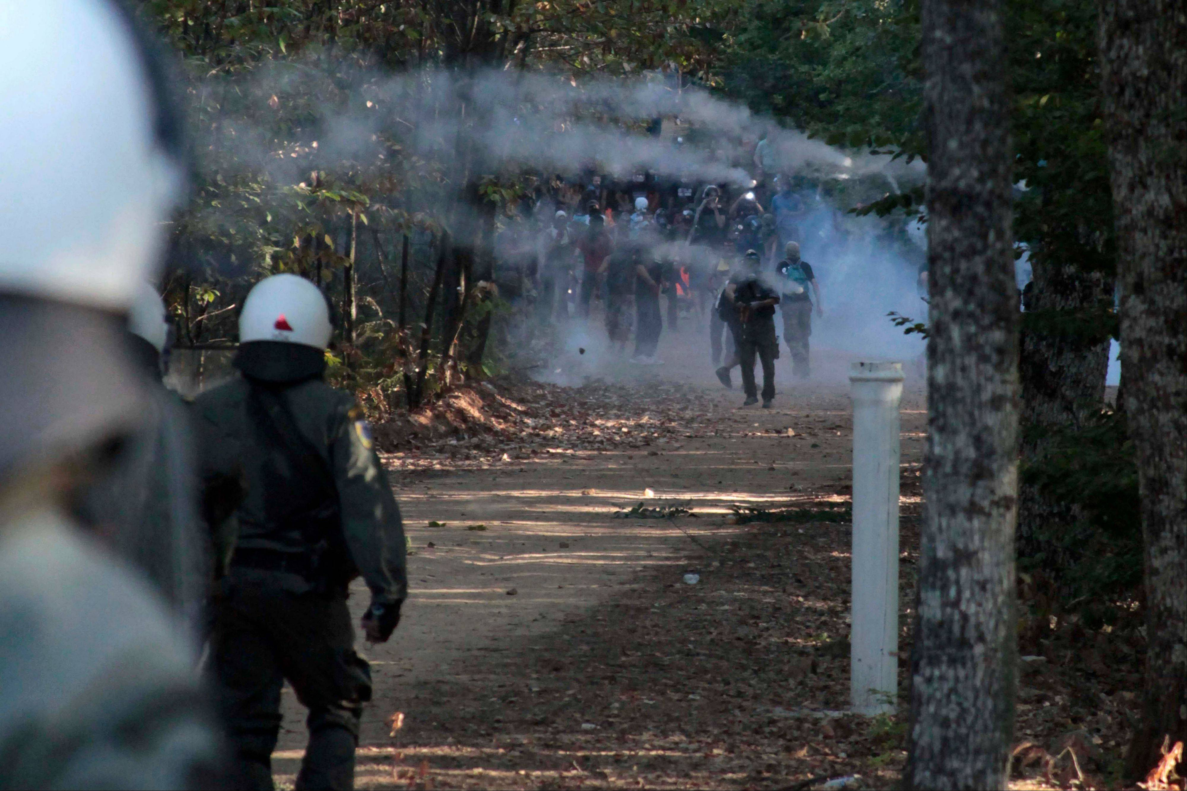 Riot police confront protesters in northern Greece's Halkidiki peninsula on Sunday. Hundreds of protesters have battled riot police for hours over plans for a gold mine in northern Greece's Halkidiki peninsula. Police say protesters threw firebombs at them, setting ablaze a forested area on the site.