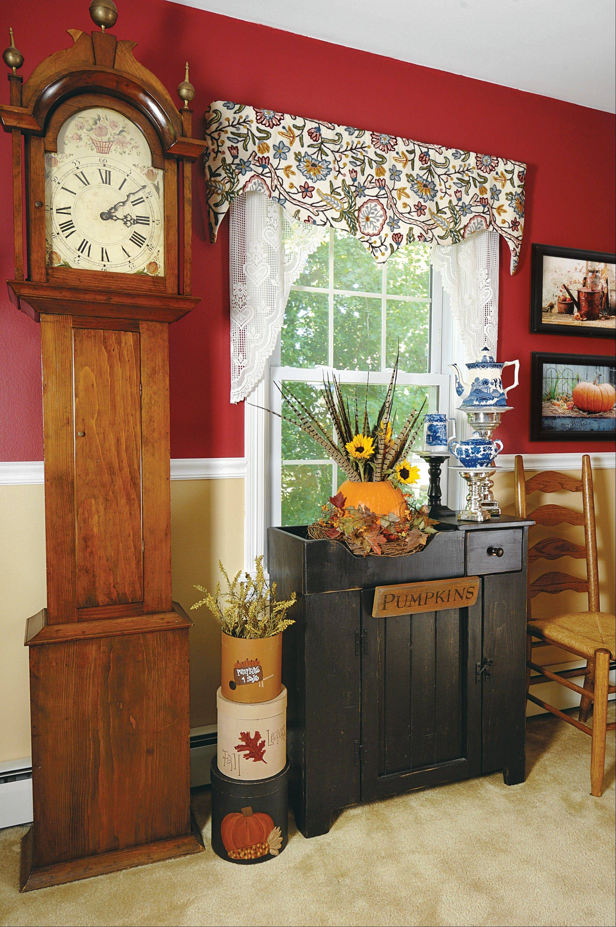 "A black dry sink contrasts nicely with the honey-hued grandfather clock. A distressed sign reading ""pumpkins"" breaks up the dry sink's front."
