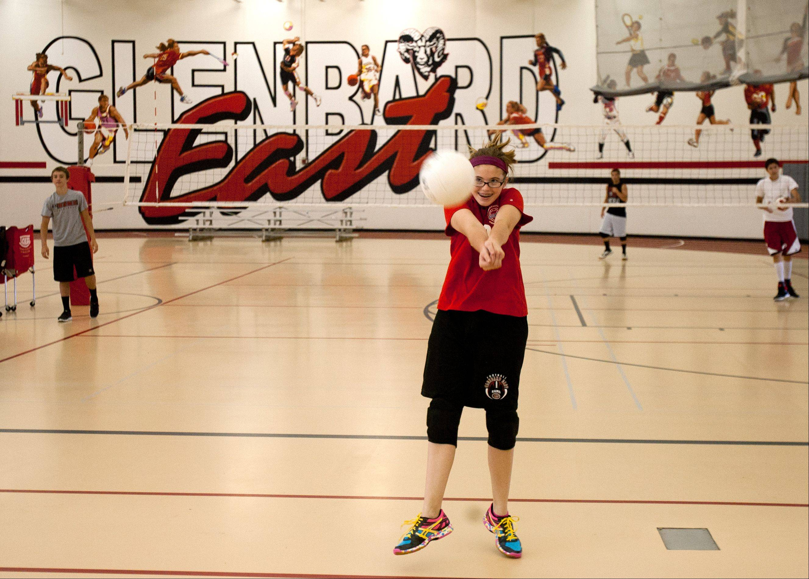 Glenbard East sophomore volleyball player Catherine McKinney returns a practice volley during a coed summer camp at the Lombard school. Catherine said the school does a good job of offering equal athletic opportunities for girls and boys.