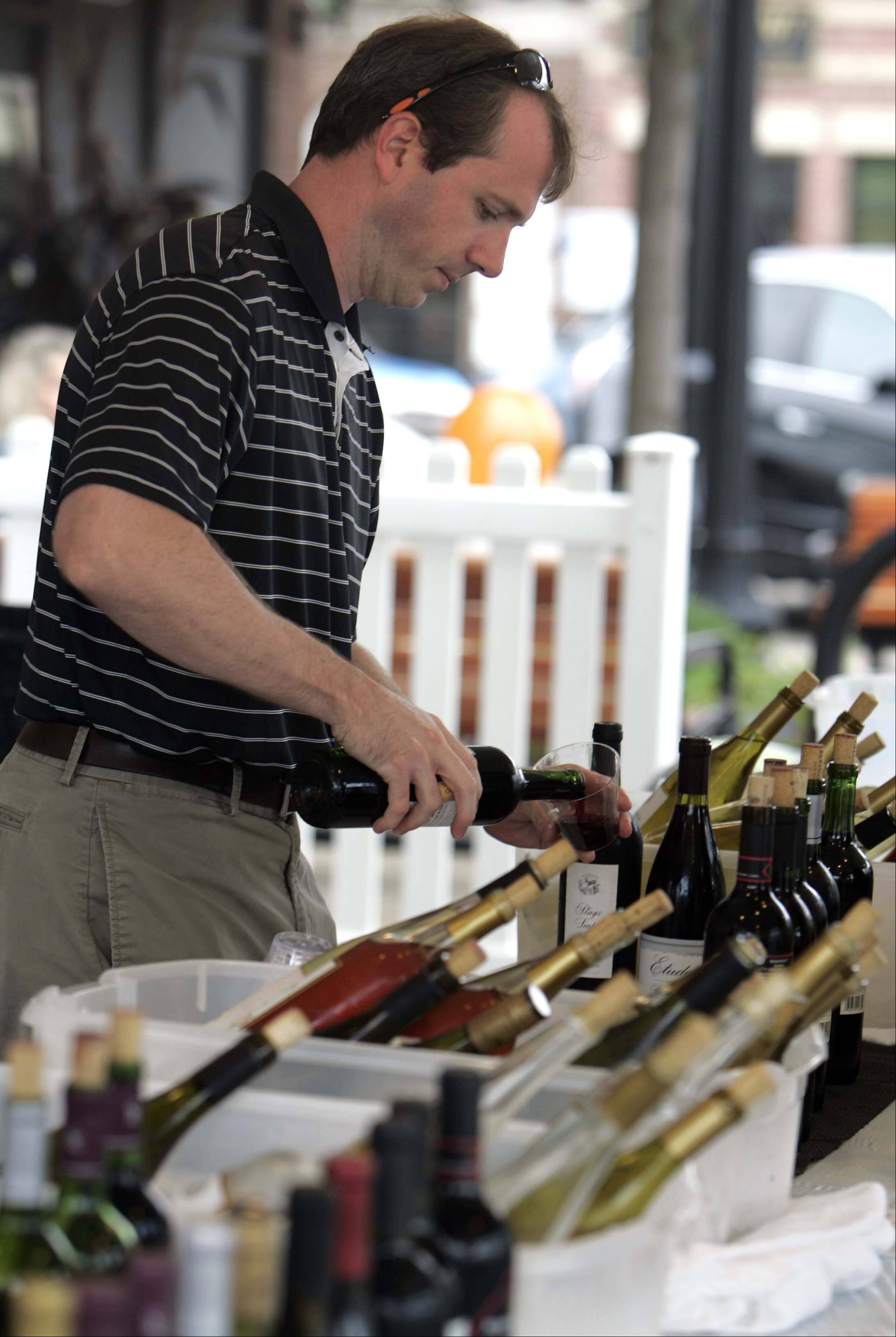 Emmett Malloy pours a glass of wine for a customer during last year's Festival of the Vine in Geneva. This year's fest ends Sunday.