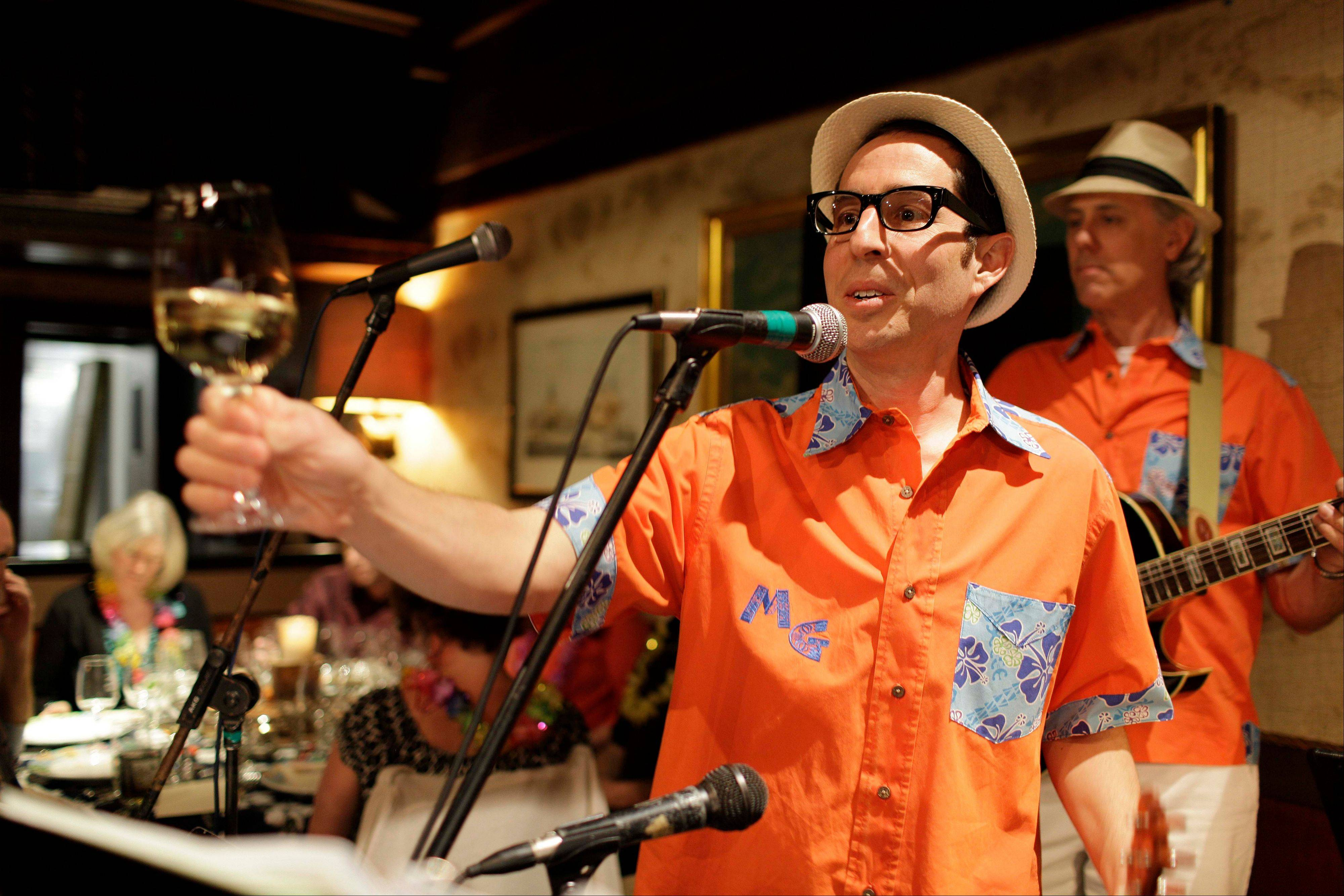 Winemaker Judd Finkelstein of Judd's Hill winery, makes a toast before playing his ukulele with his band during a winery luau at Trader Vic's restaurant in Emeryville, Calif.